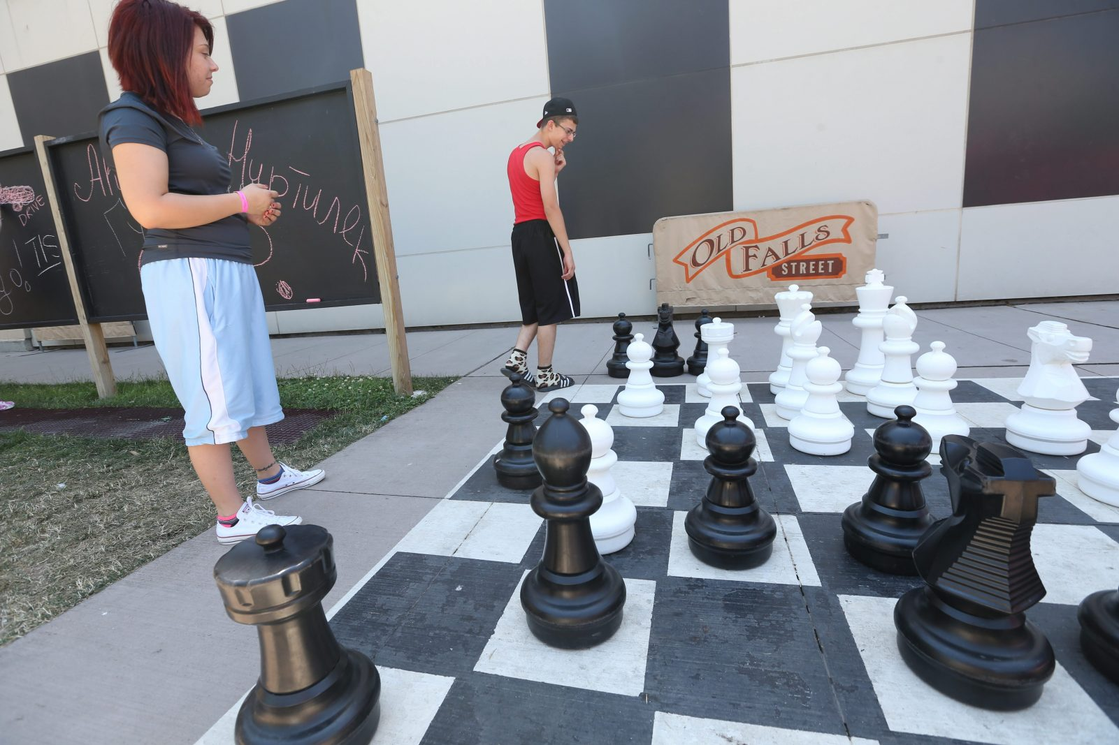 Old Falls Street in Niagara Falls has various activities for the family. Alex DeSena, 17, right, of Queens, and his sister Kaitlin DeSena, 22, of Cape Coral, Florida, play a giant sized chess game in an area filled with games and adirondack chairs, Tuesday, July 5, 2016. The siblings are visiting family. (Sharon Cantillon/Buffalo News)