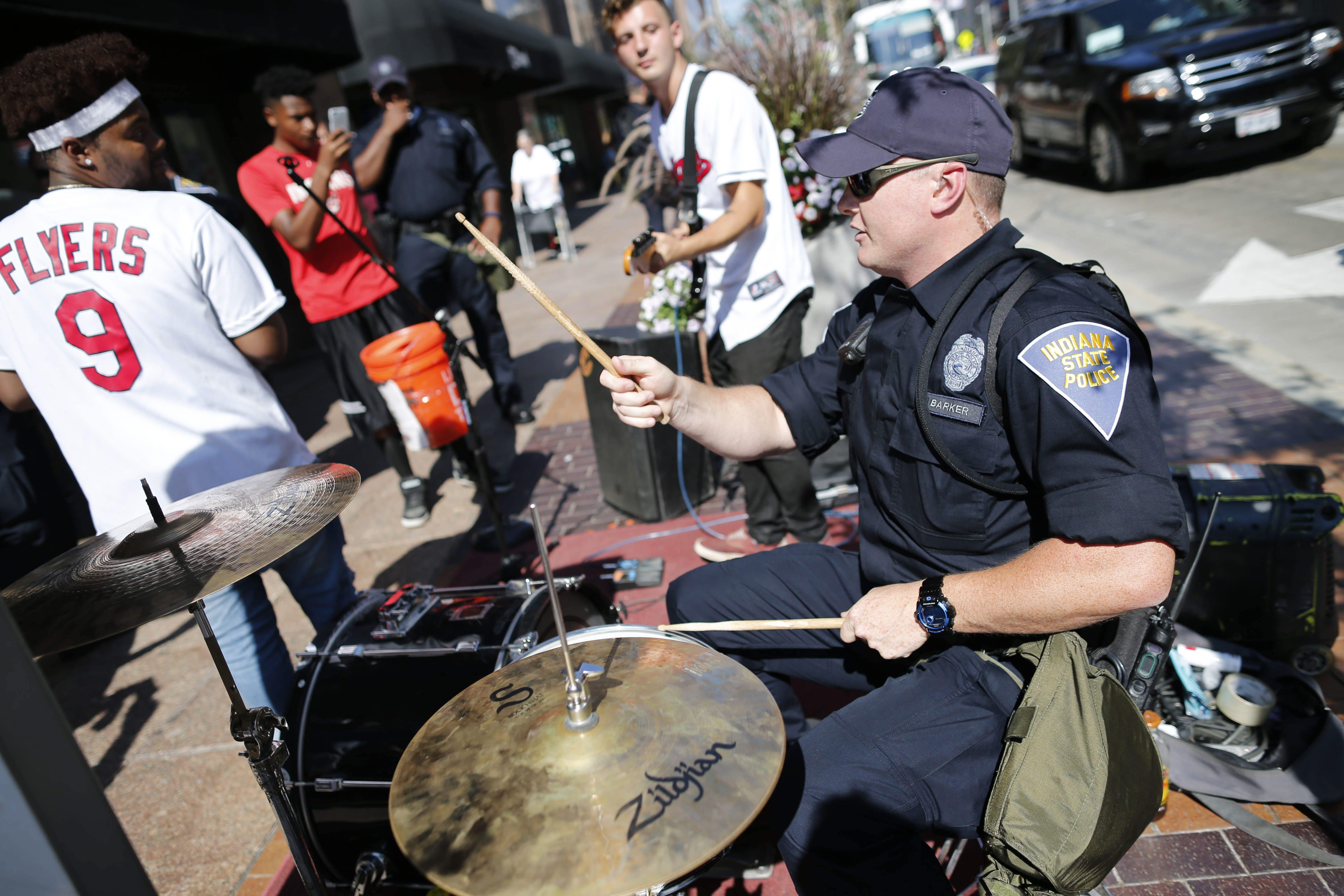 An Indiana State Police officer sits in on drums with the band Talionis as they perform on Euclid Avenue outside the RNC in Cleveland, Wednesday, July 20, 2016. (Photo by Derek Gee)