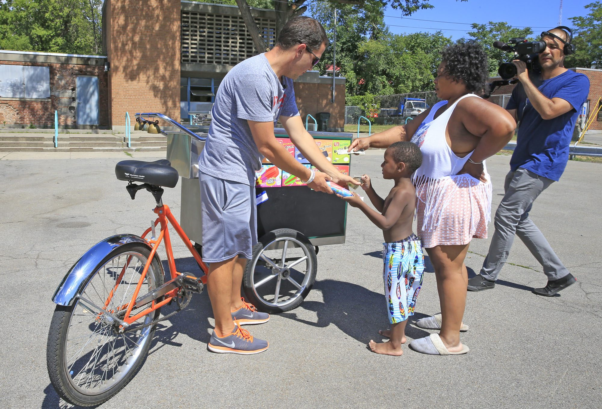 """A German film crew (RTL) films James Karagiannis, AKA """" James the Ice Cream Cycle Dude,"""" as he sell ice cream in Shoshone Park. (Harry Scull Jr./Buffalo News)"""