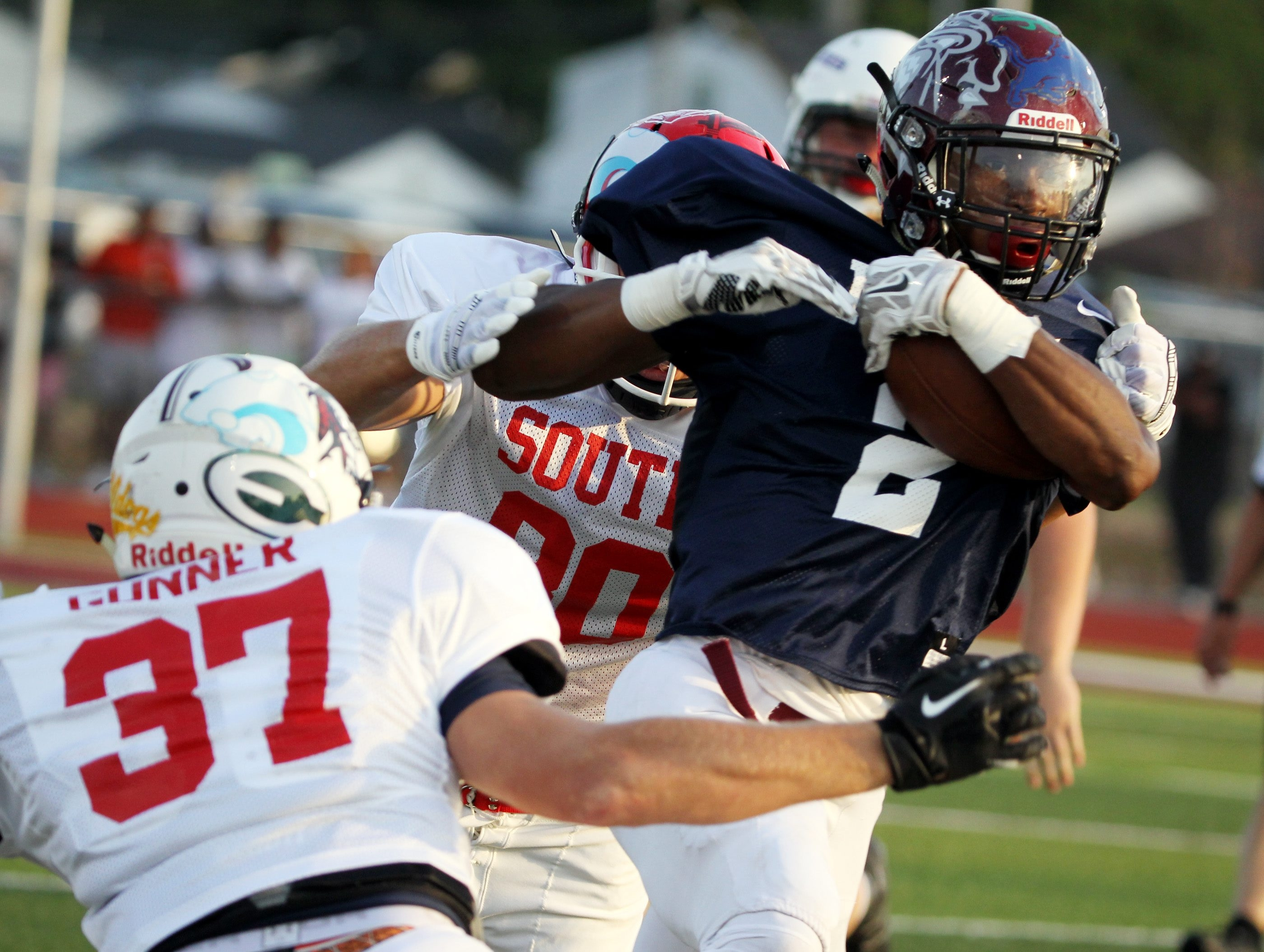 Darren Thompson of the North runs for a first down against Henry Gunner of the South in the Kensington Lions All-Star game.