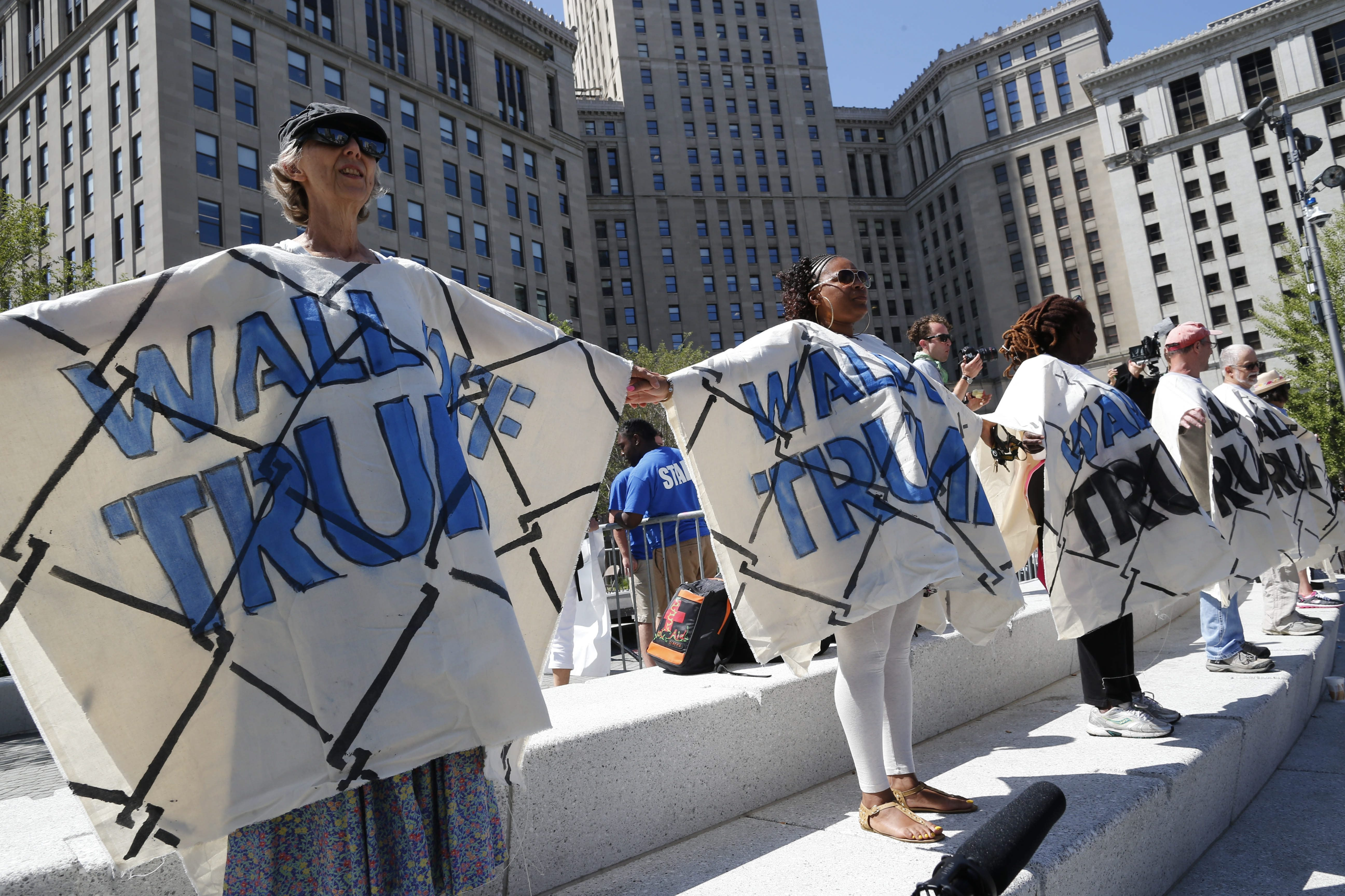 """Protesters wear faux-brick walls over their fronts and backs during the """"Wall Off Trump"""" protest in Public Square."""