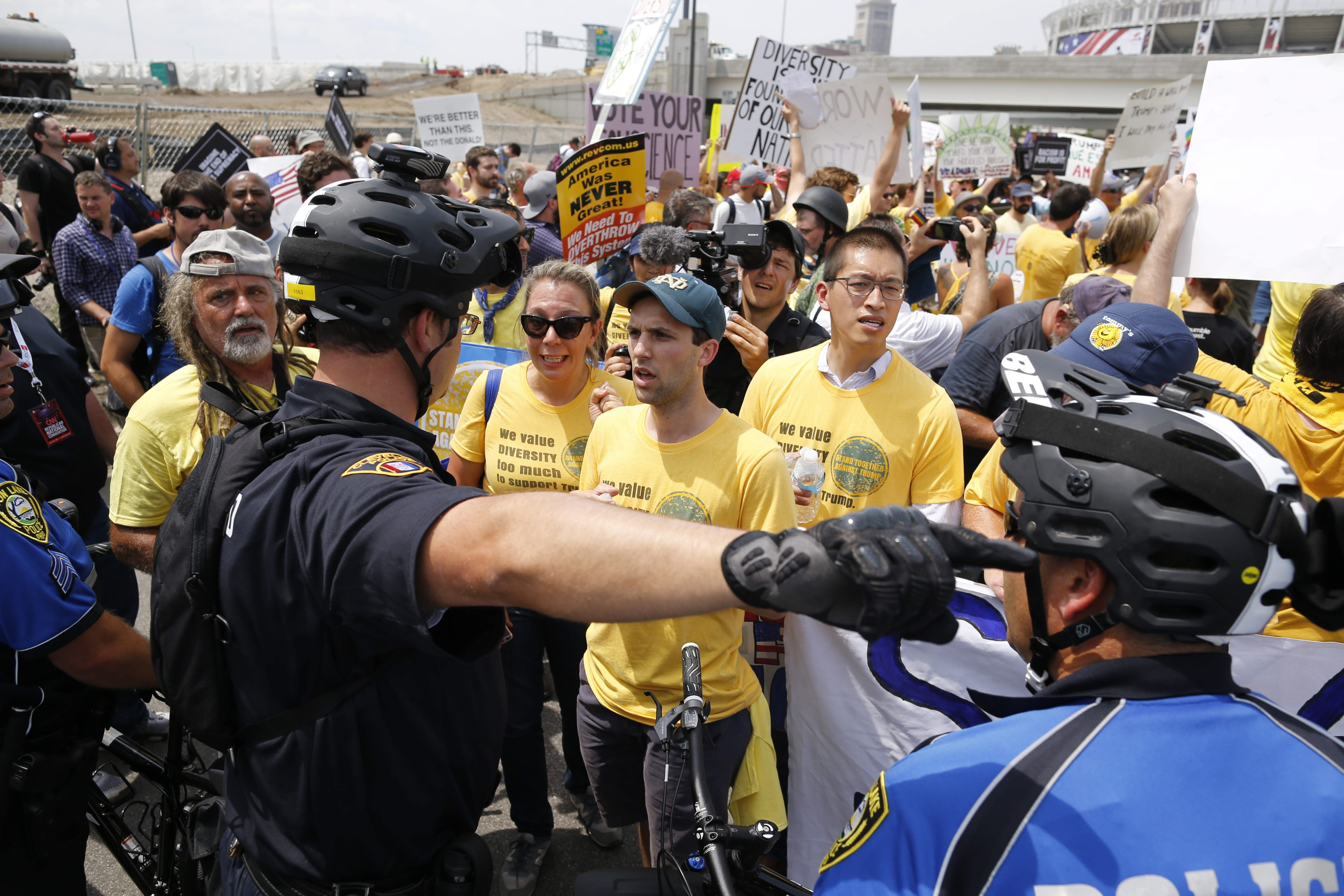 "Protesters marching in the ""Stand Together Against Trump"" parade in Cleveland encounter a line of police officers at the I-190 overpass, preventing them from proceeding to the end of the city-authorized parade route, Thursday, July 21, 2016.  (Photo by Derek Gee)"