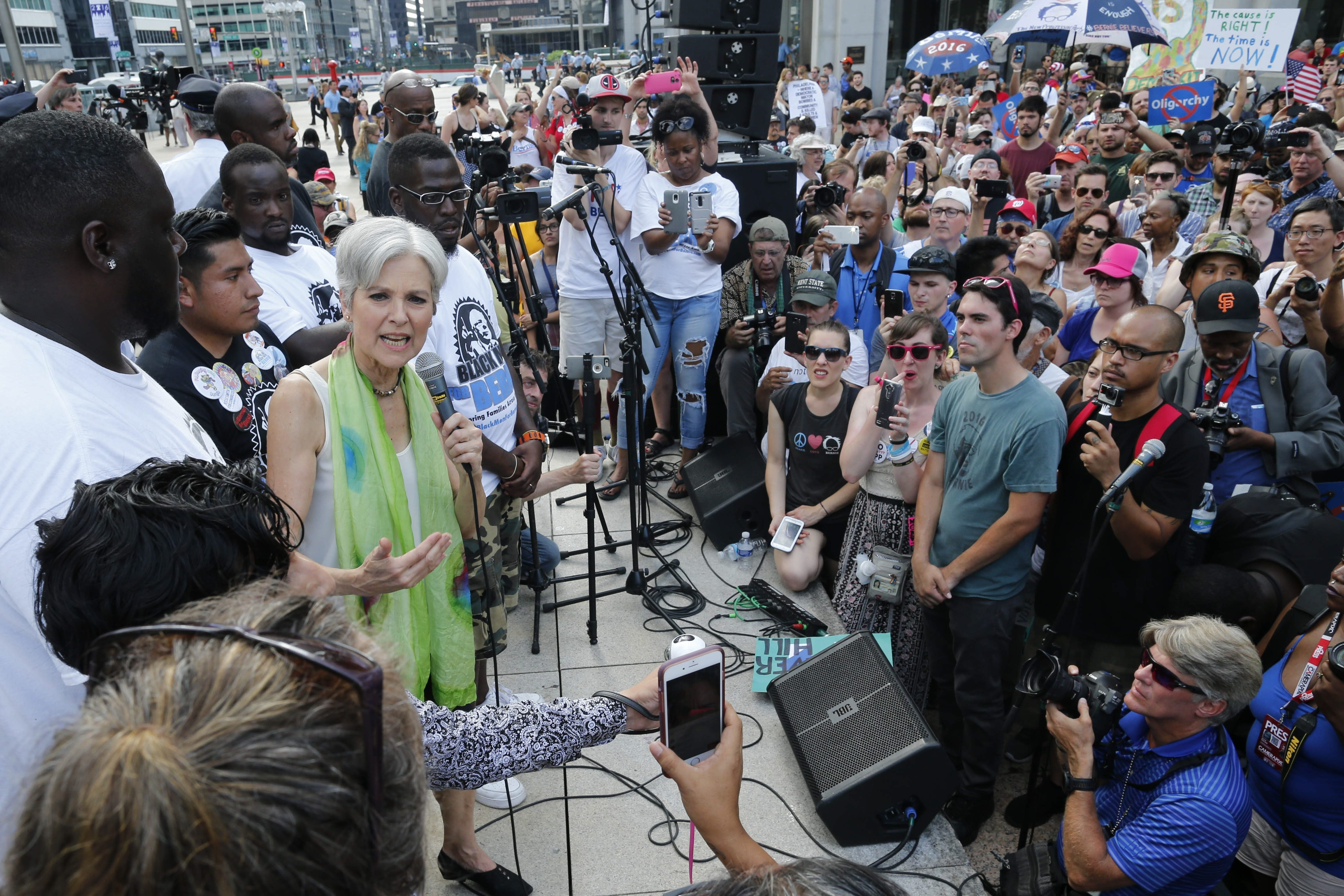Green Party candidate for president Jill Stein, in green scarf, speaks on stage at a Black Men for Bernie rally in Thomas Paine Plaza in Philadelphia, Wednesday, July 27, 2016.  (Photo by Derek Gee)