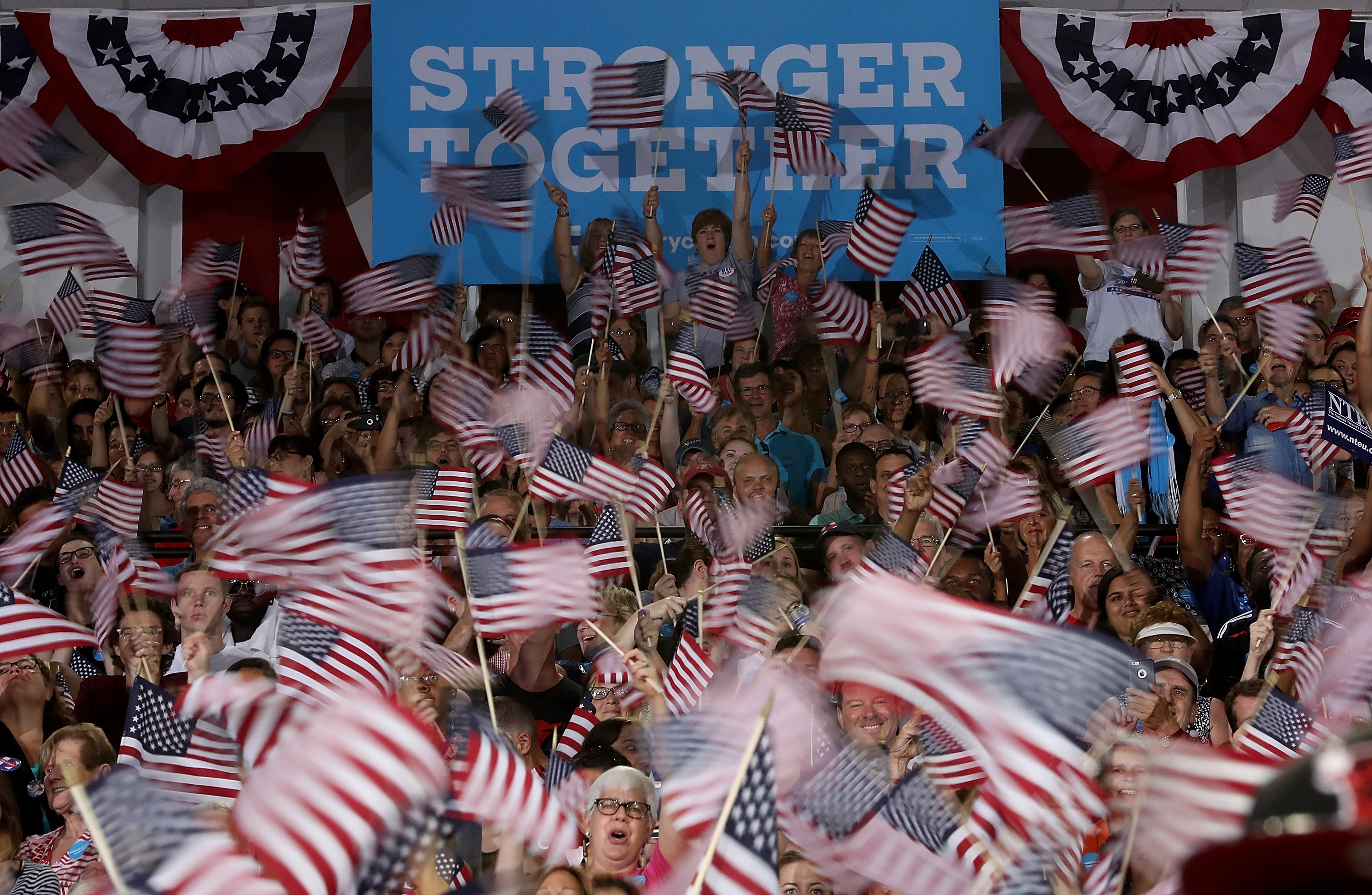 Supporters wave flags during a campaign rally with democratic presidential nominee former Secretary of State Hillary Clinton and democratic vice presidential nominee U.S. Sen. Tim Kaine at Temple University on July 29, 2016 in Philadelphia. (Justin Sullivan/Getty Images)