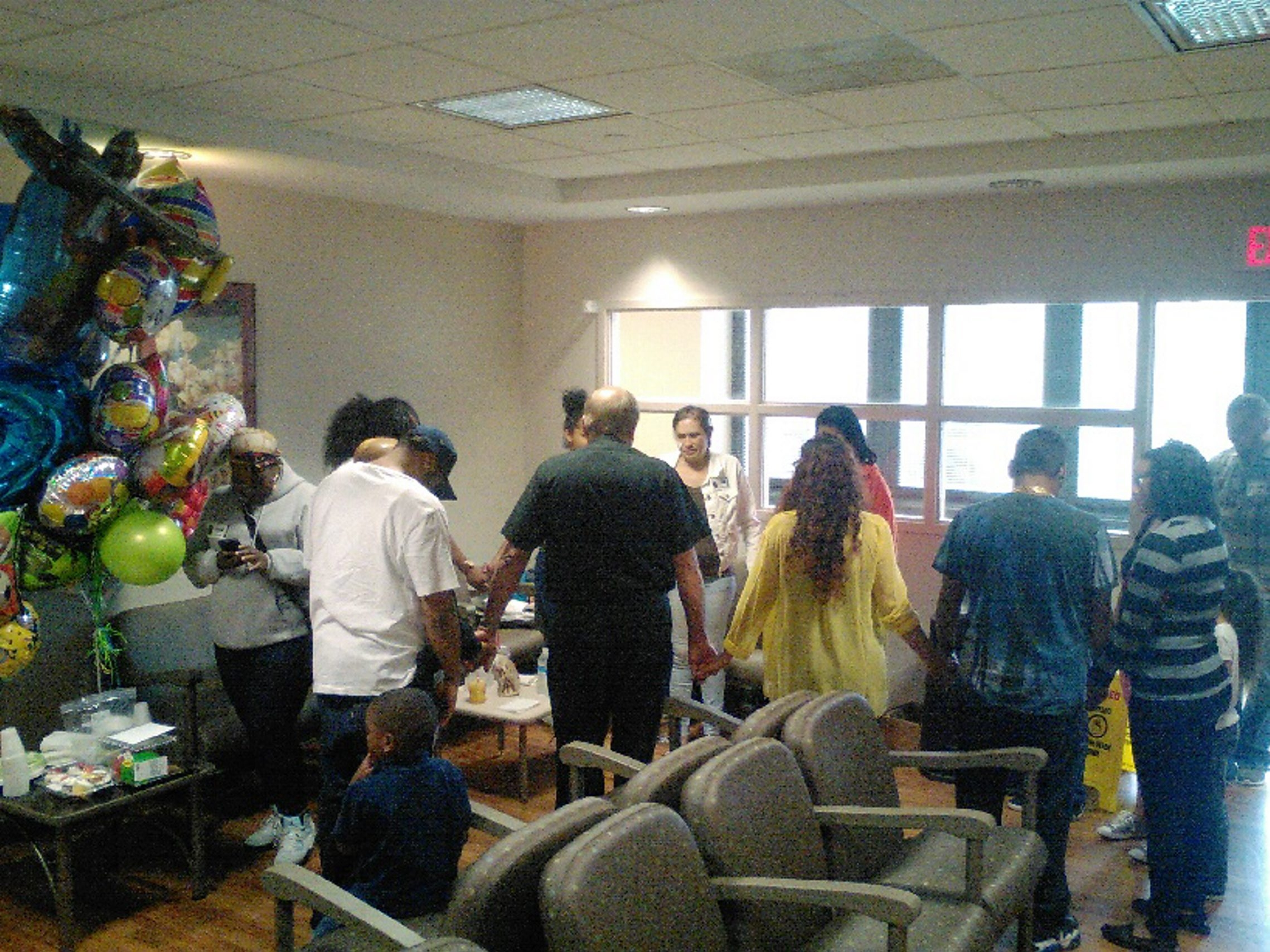 Above, relatives hold hands and pray for shooting victim Juan Rodriguez, inset left, in the intensive care unit at Erie County Medical Center on Friday, the boy's 12th birthday.