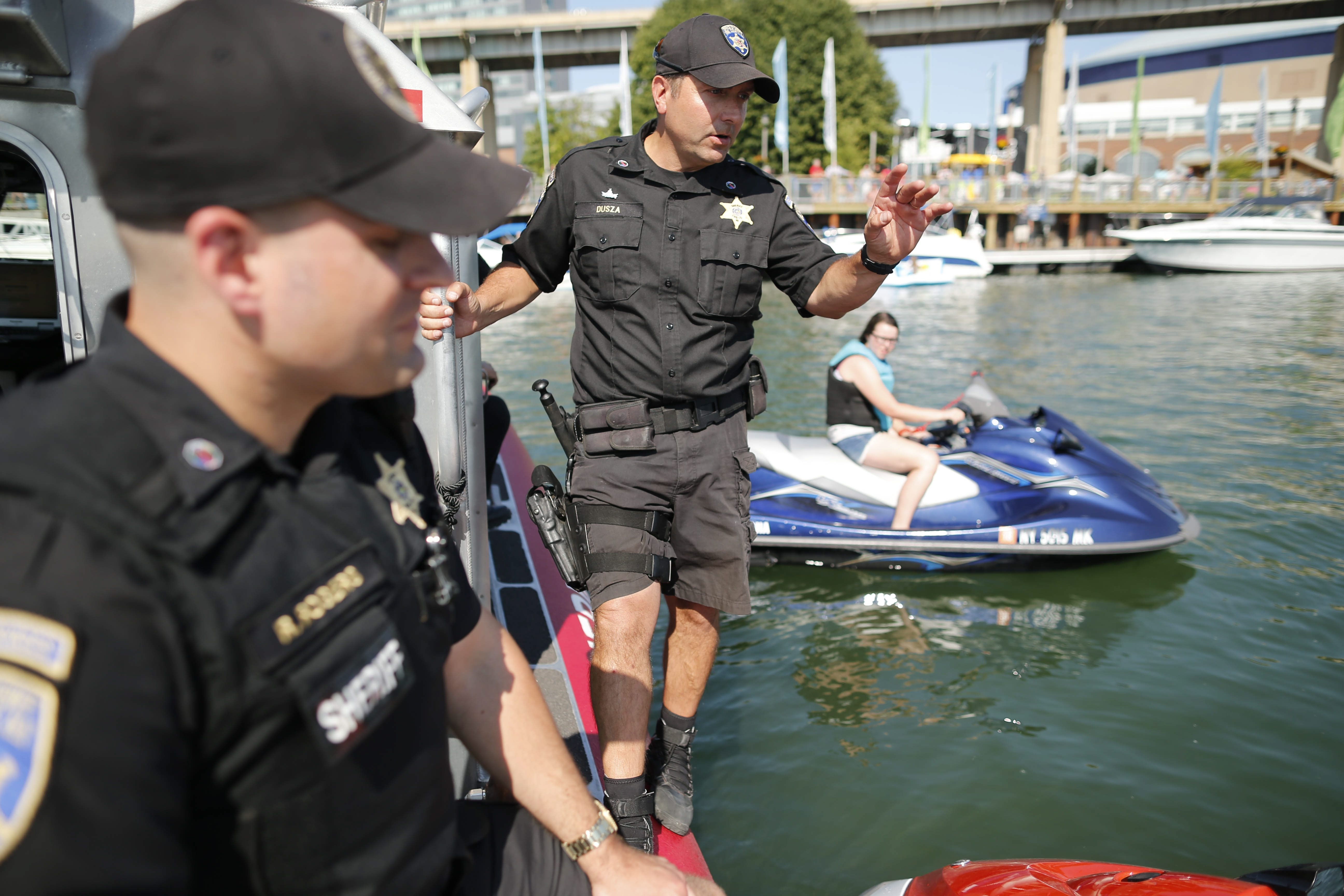 Erie County Sheriff Deputies Ryan Rogers, left, and Tim Dusza, right, chat with jet skiers during a safety inspection off of Canalside in the Buffalo River, Friday, June 24, 2016.  Dusza is giving advice about having a whistle easily accessible for the sake of safety.  The jet skiers passed the inspection.  (Derek Gee/Buffalo News)