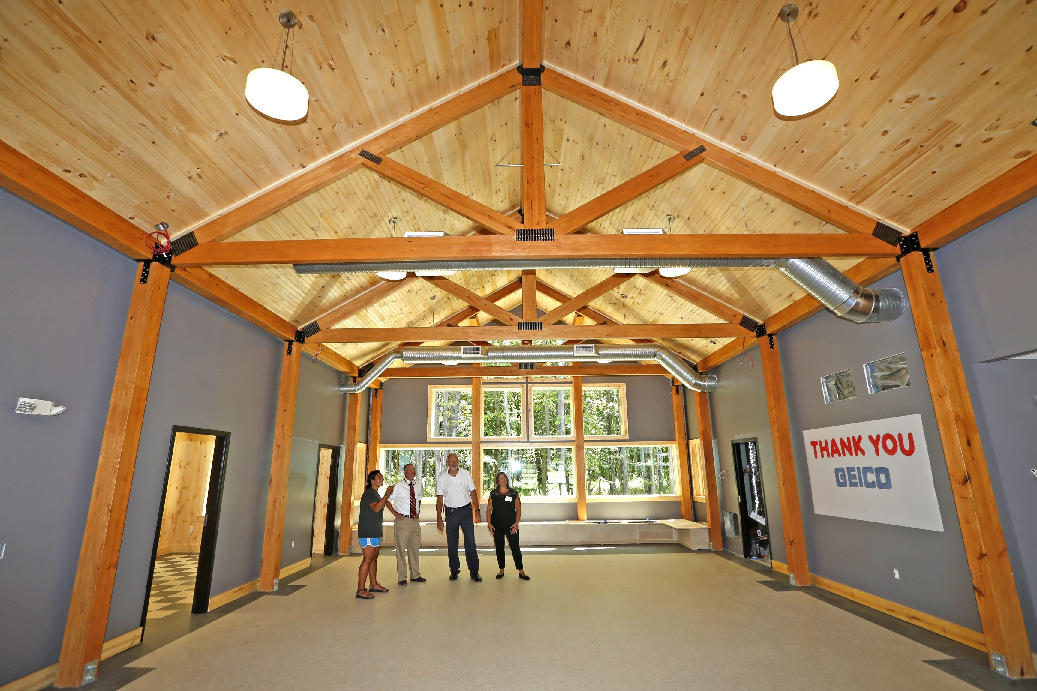 Officials show off the main hall of the new GEICO Woodland Lodge at Cradle Beach in Angola on Monday. The 4,500-square-foot building  is designed to accommodate 40 children and adults overnight. (Robert Kirkham/Buffalo News)