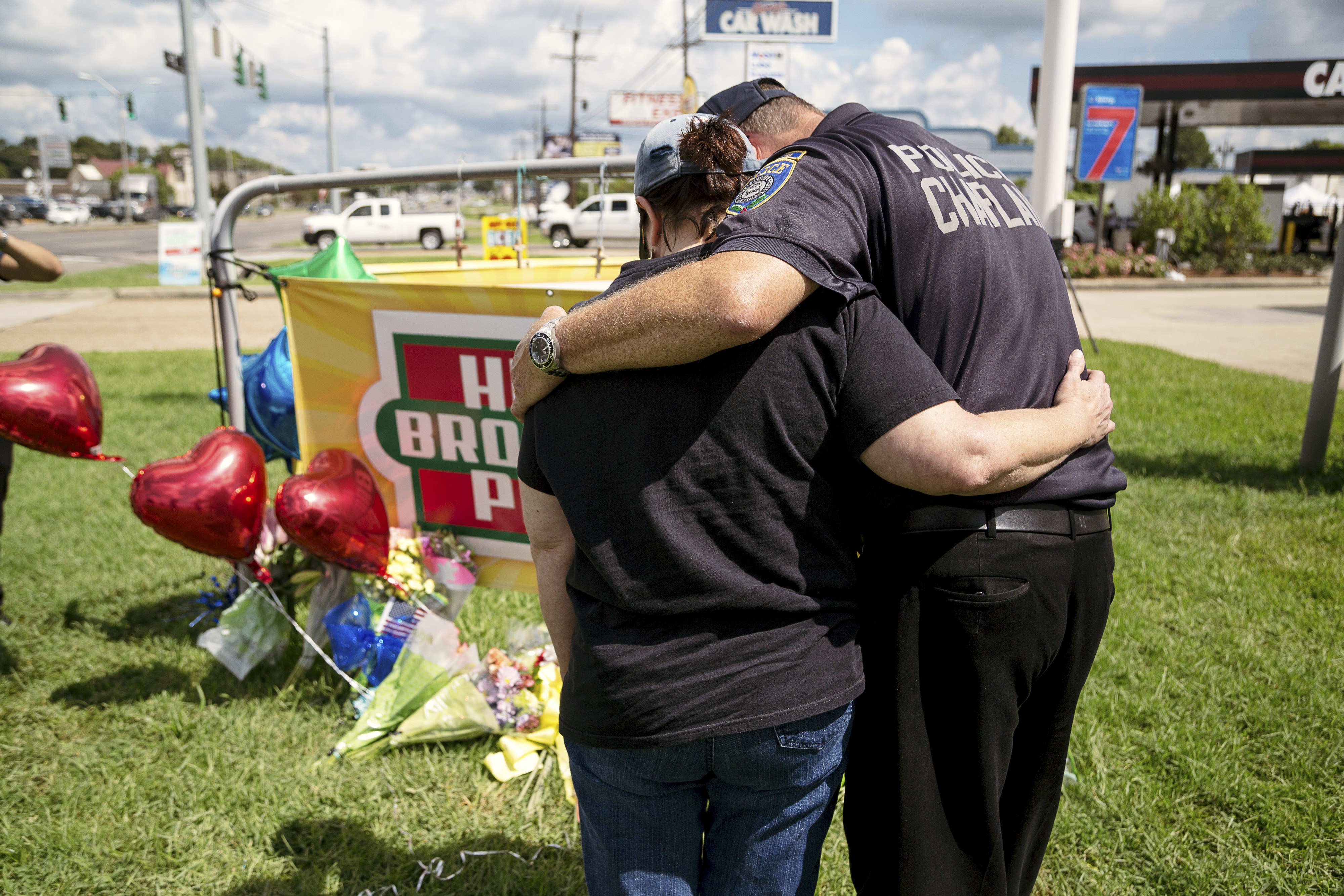 Robert Ossler, a police and fire chaplain, embraces LaNette Drury at a makeshift memorial at the site in Baton Rouge where three police officers were shot to death.