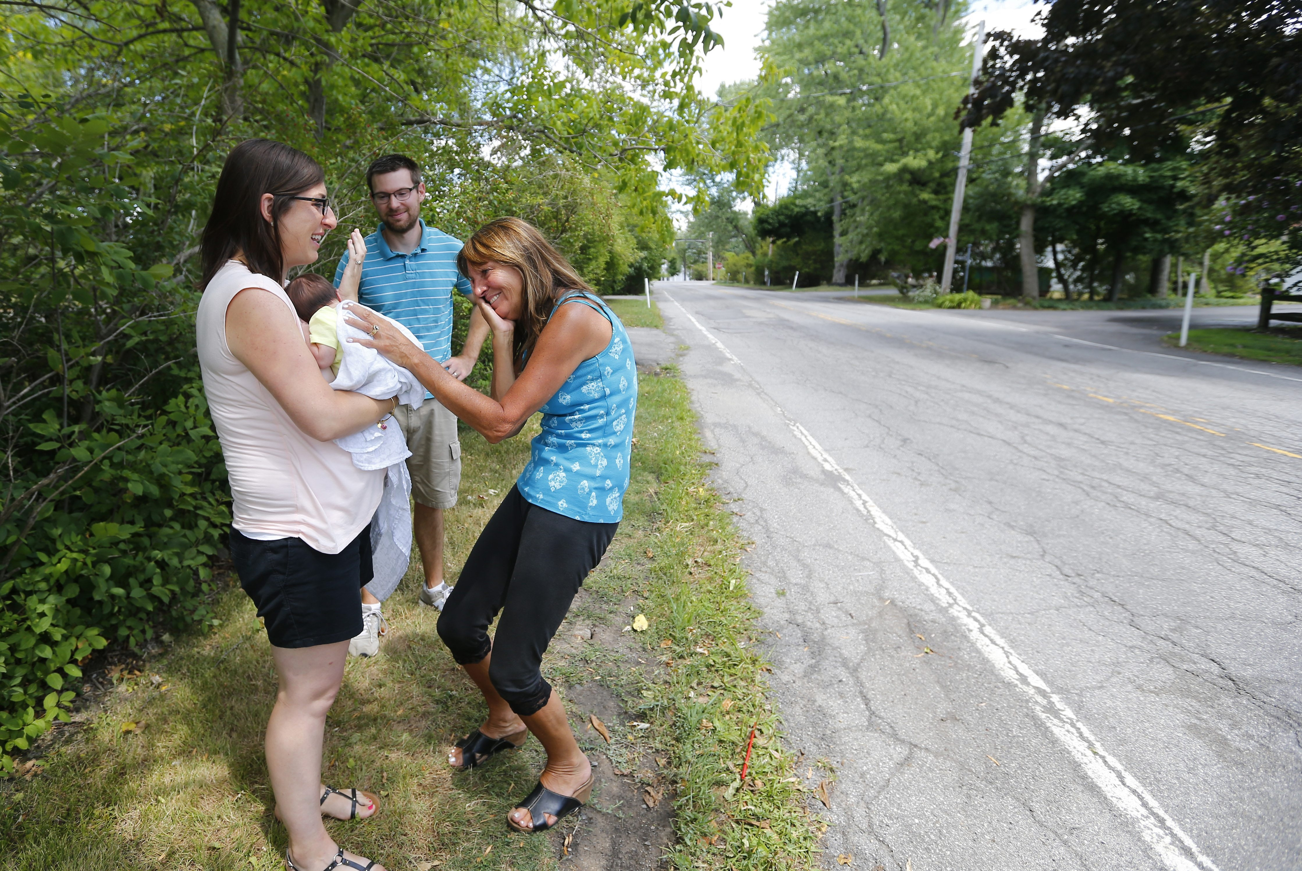 Amanda and Matthew Colebeck and infant Paige on Tuesday meet Kathy Barnes, right, the motorist who stopped to offer assistance Friday on Park Club Lane in Amherst where Paige was born.
