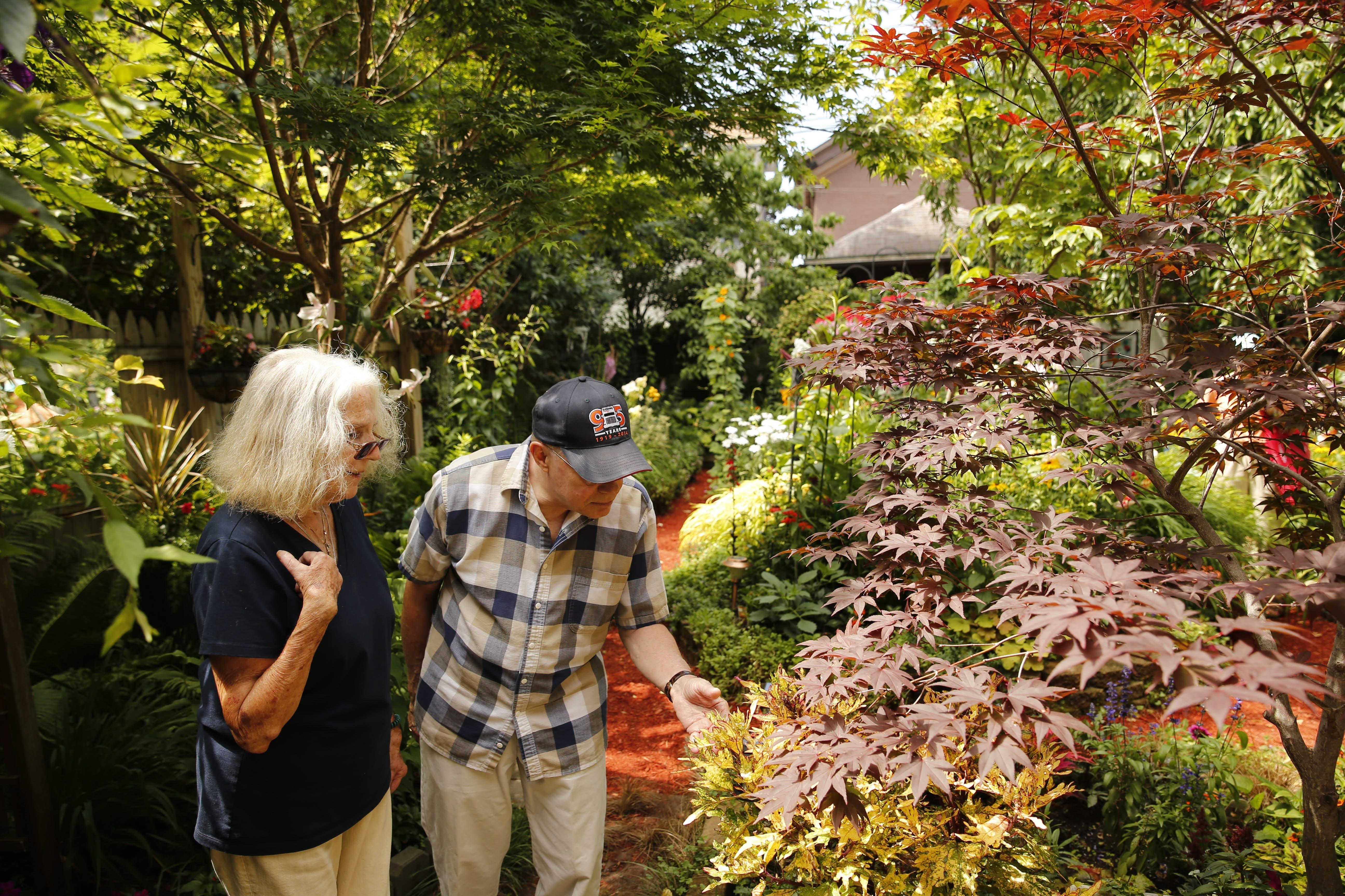 Neighbor Edith Bartlett and David Krellner tour the garden of Jim Ecker on Johnson Park during last year's Garden Walk.  (Derek Gee/Buffalo News)