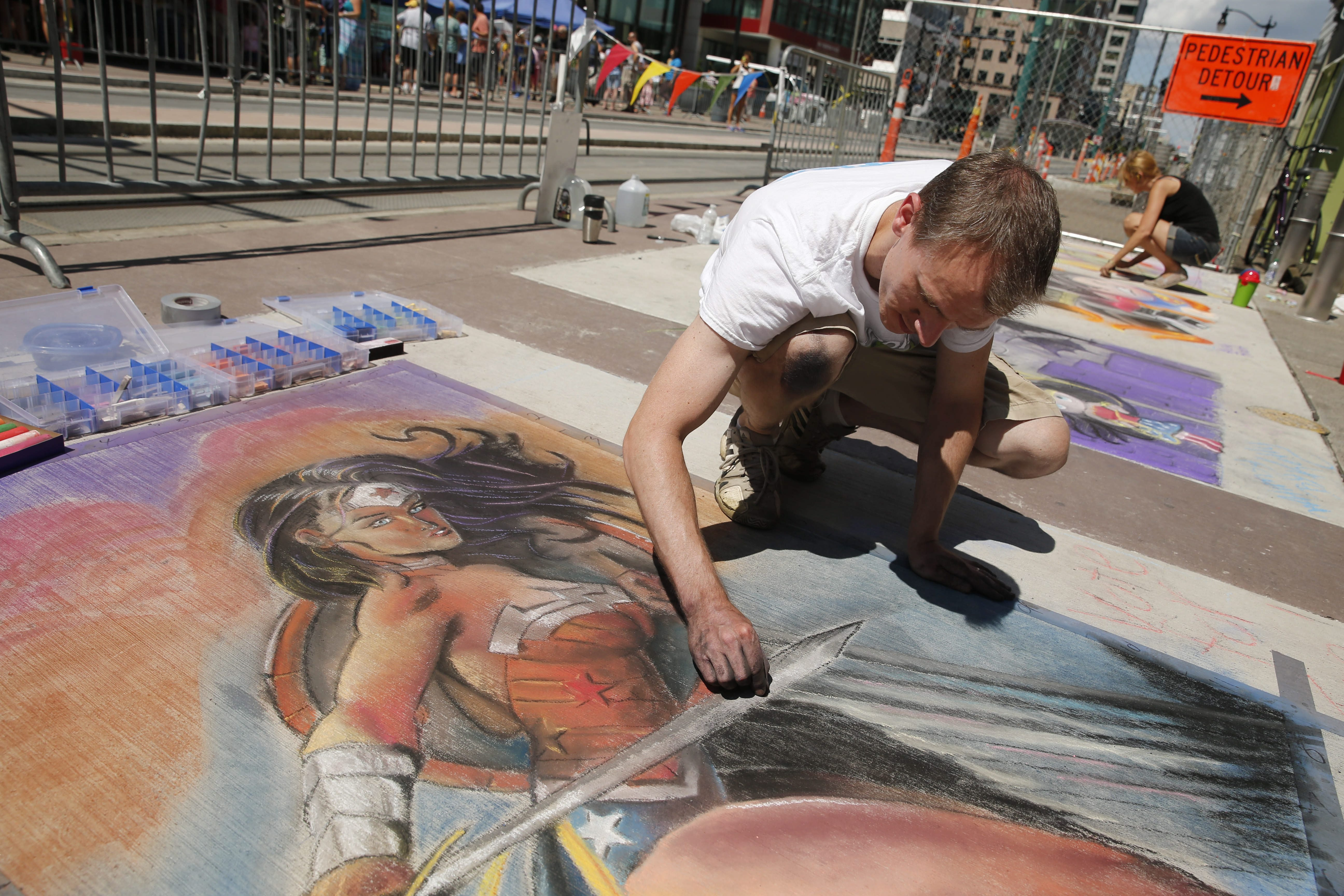 Joe Mahley of Lockport draws Wonder Woman at ChalkFest Buffalo on the 500 block of Main Street, Saturday, Aug. 1, 2015.  (Derek Gee/Buffalo News)