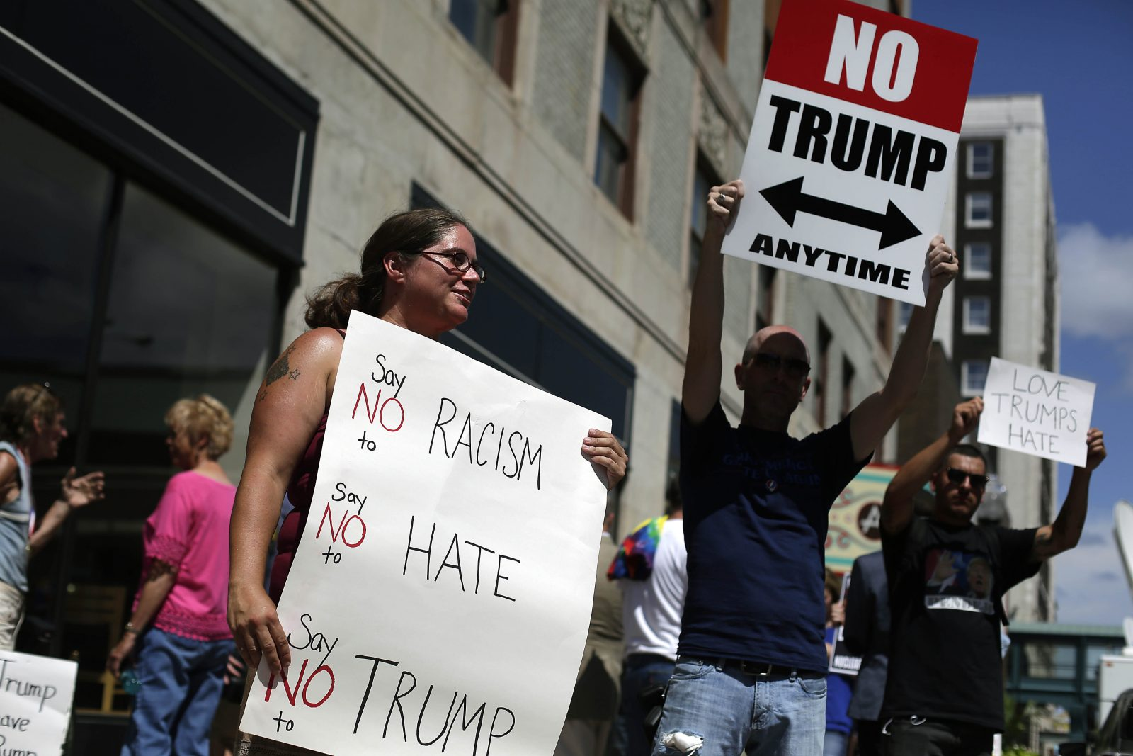 DAVENPORT, IA - JULY 28: Demonstrators hold signs as they protest Republican Presidential candidate Donald Trump during a campaign event for Trump on July 28, 2016 in Davenport, Iowa. Trump, who received the Presidential Republican nominee last week during the Republican National Convention will face Democratic Presidential candidate Hillary Clinton during the November general election. (Photo by Joshua Lott/Getty Images)