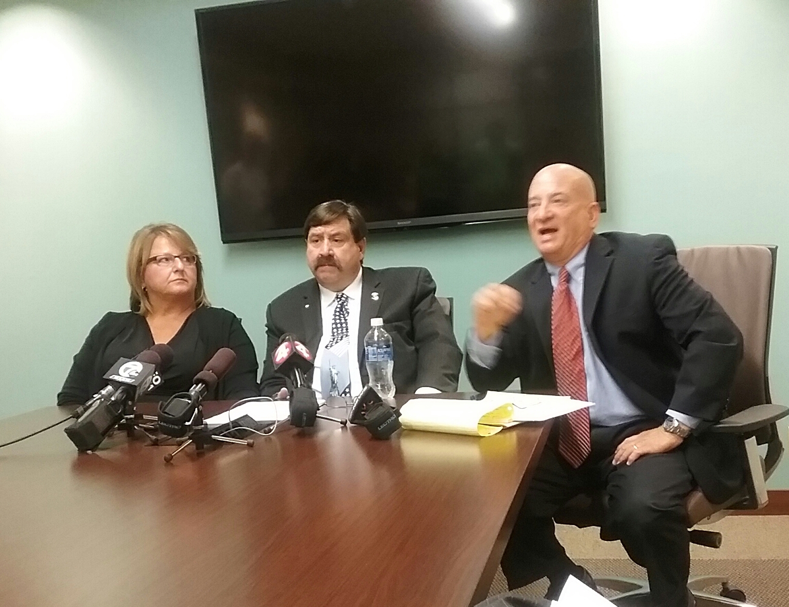 Chief James Michel with his wife, Sandy, and lawyer Howard Cohen at Friday press conference.