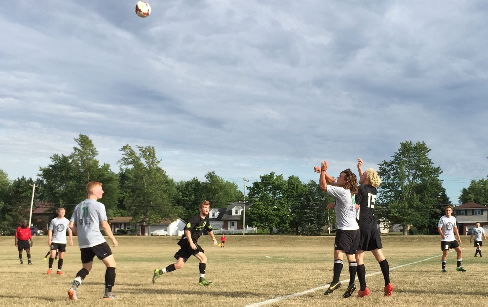 Ross Suitor, in black, and Dan Warner jump for a header in Week 10 action between Queenston and Celtic United. (Ben Tsujimoto/Buffalo News)