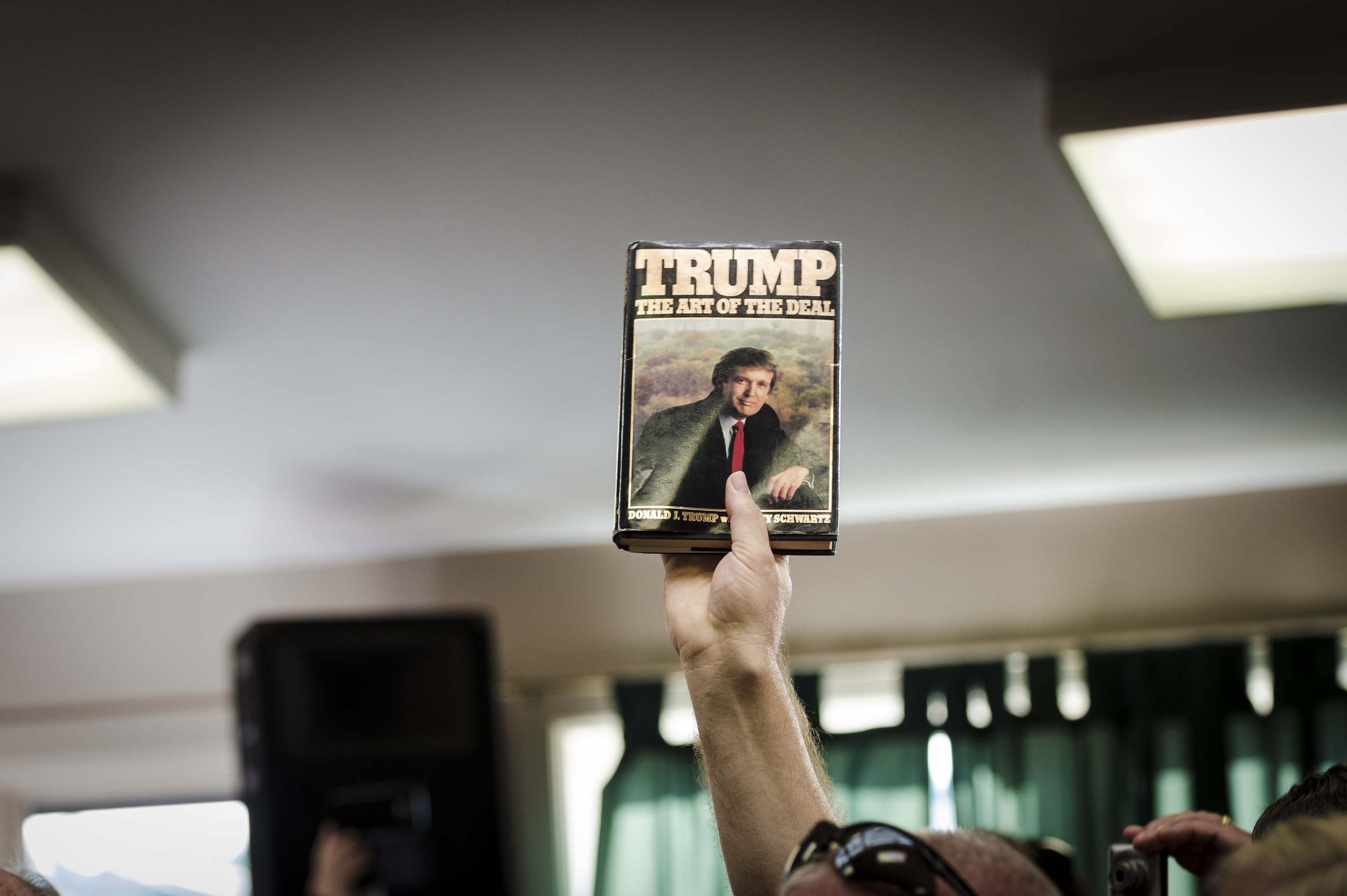 A supporter holds up a copy of Donald Trump's book 'The Art of the Deal,' by Tony Schwartz, at a rally in Laconia, N.H. (Ian Thomas Jansen-Lonnquist/The New York Times)