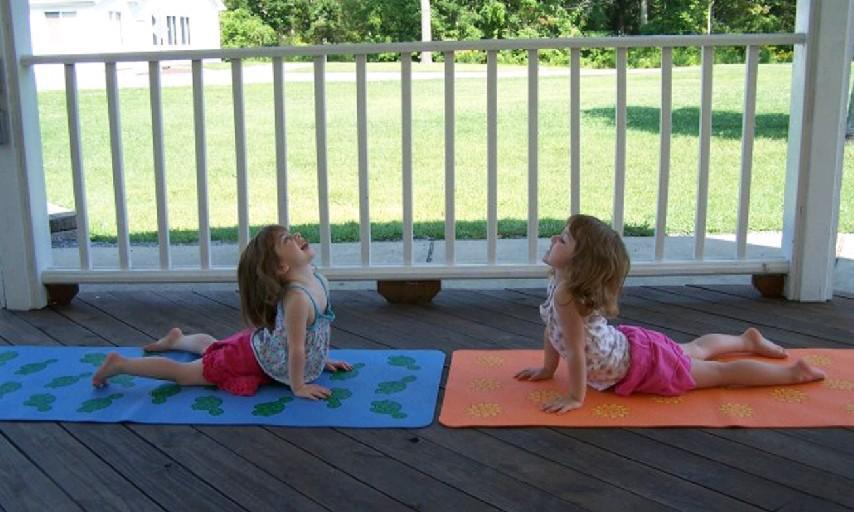 Iris Leatherbarrow, left, and her sister, Mica, pictured in the cobra yoga pose, often help their mother, Julie, teach her Budding Tree Yoga classes. (Julie Leatherbarrow/Special to the News)