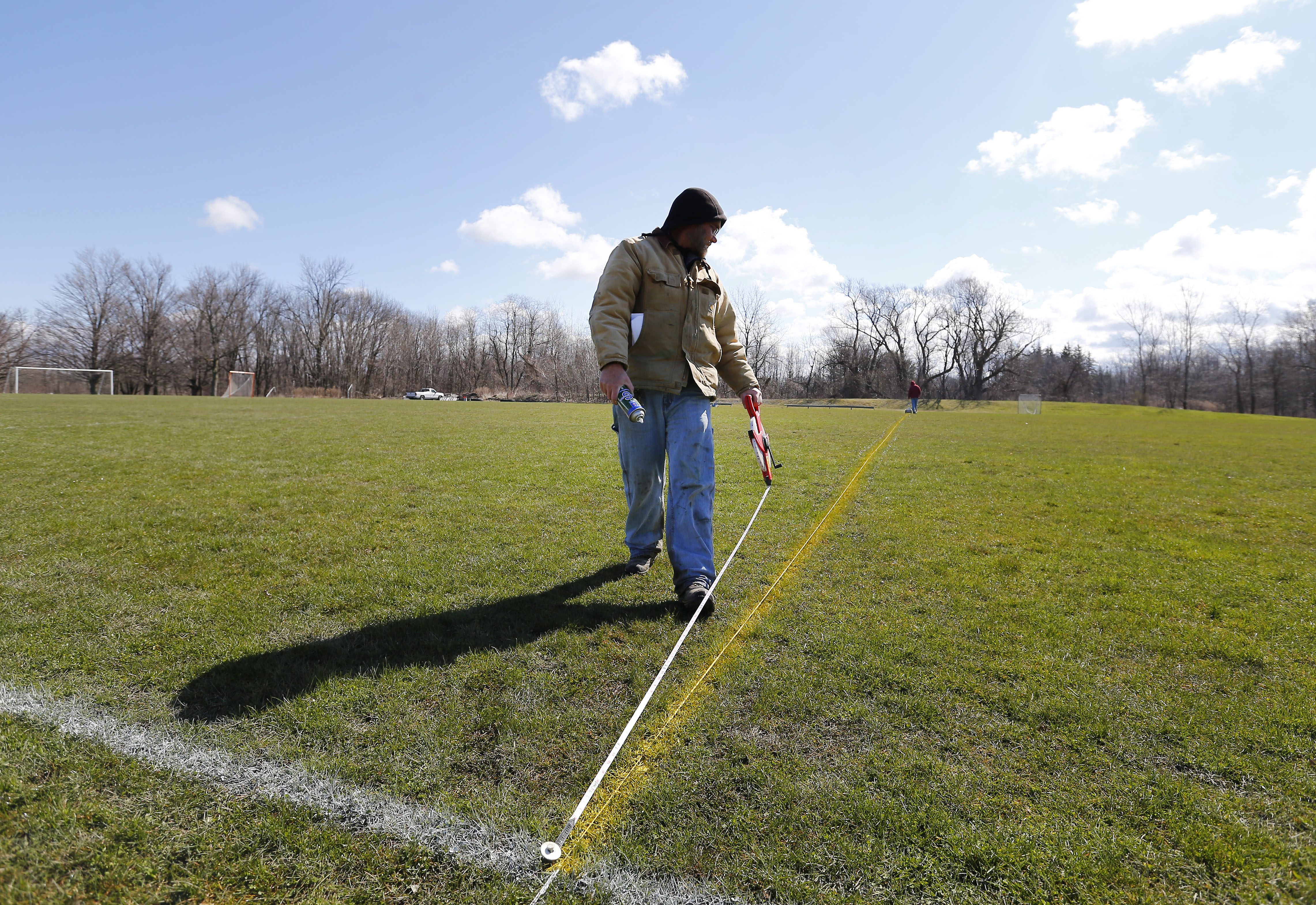 Tom Bapst measures the field as he paints the lines on the lacrosse field at Hilbert College in Hamburg Tuesday, April 12, 2016. (Mark Mulville/Buffalo News)