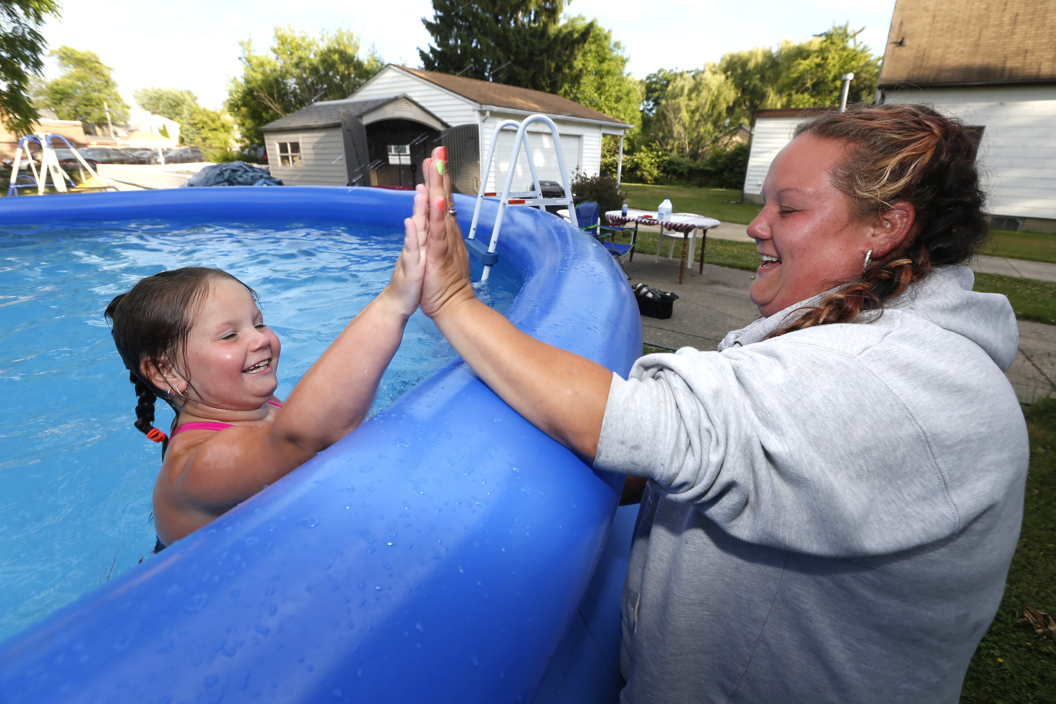 "With a watchful eye from her mom, right, Mackenzi McMullen, 7, cools off in an above ground pool her single-mom Amber Watroba provided for her from extra money she set aside from her nursing home aid paycheck. Her mom claims she doesn't need the millions of dollars a lucky lottery ticket would provide, but ""a couple thousand would be nice"" to ""fix things"" in her rented apartment on Linden Street in Lackawanna. (Robert Kirkham/Buffalo News)"