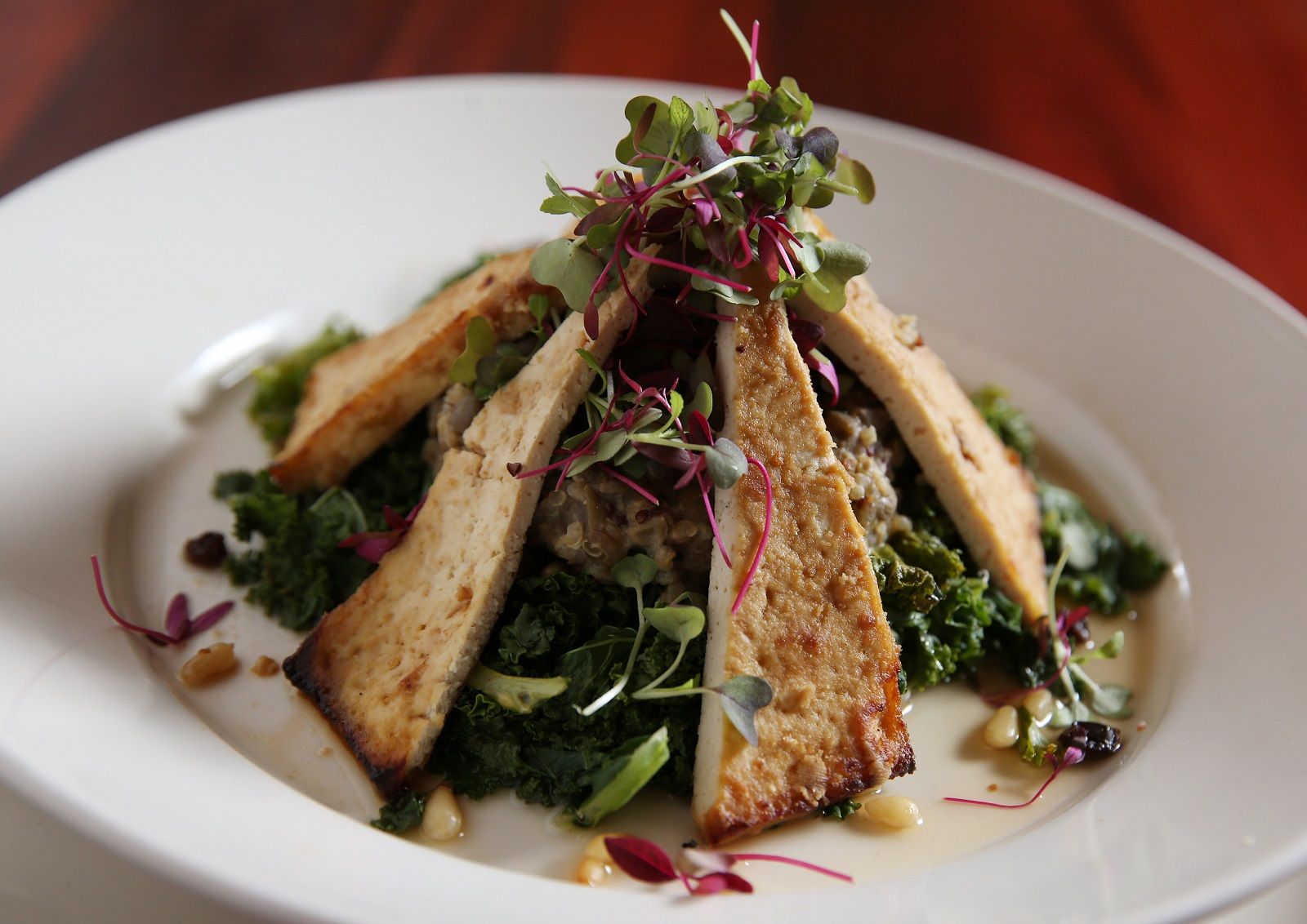 The Steer serves a marathon bowl which is made with steamed kale, lentils, quinoa, pine nuts, dried currants, grilled orange miso and tofu steak. (Sharon Cantillon/Buffalo News)