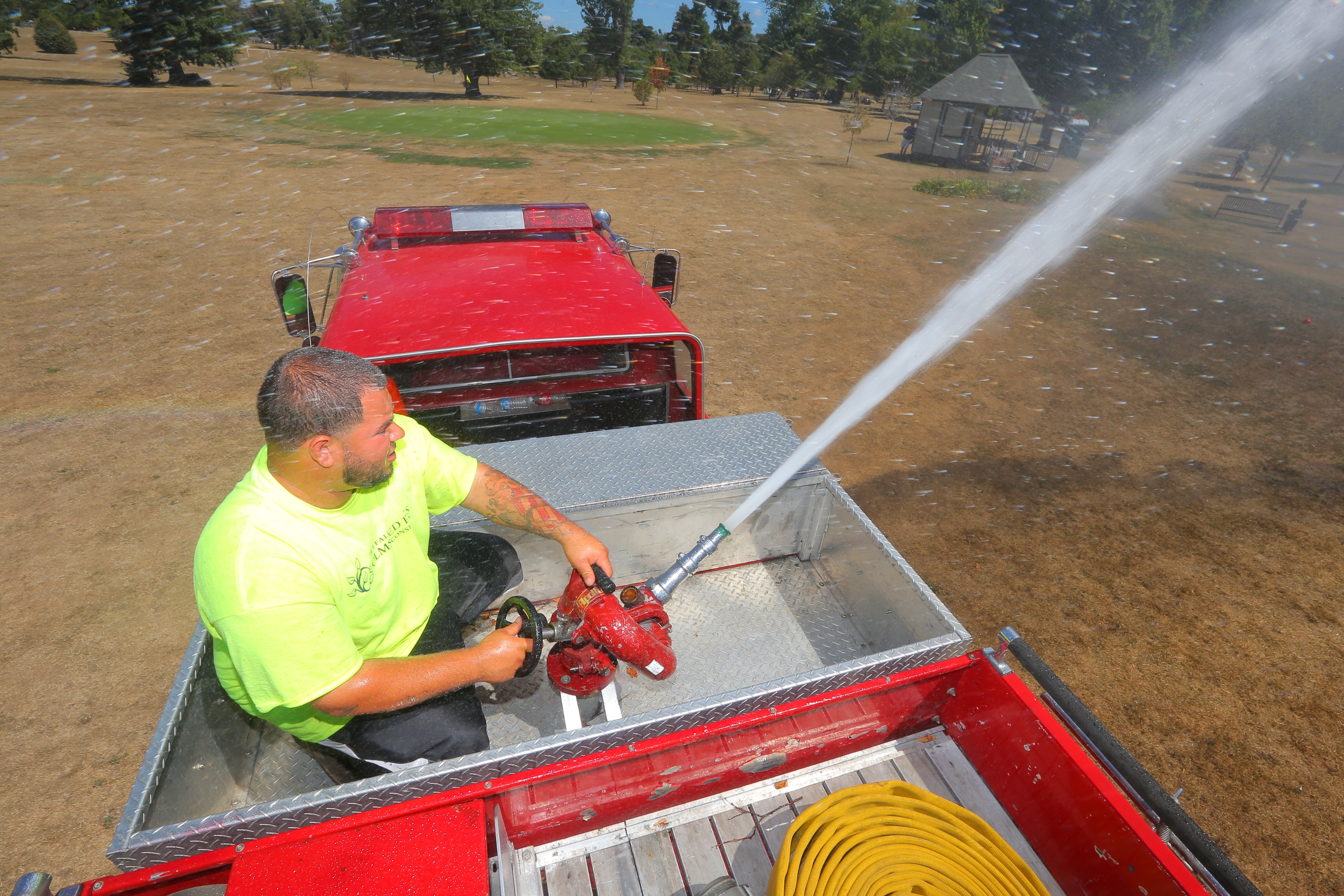 Olmsted Parks worker Jimmy Rodriguez sprays water from a pumper fire truck to water the tees and greens at the Delaware Park Golf Course. (John Hickey/Buffalo News)