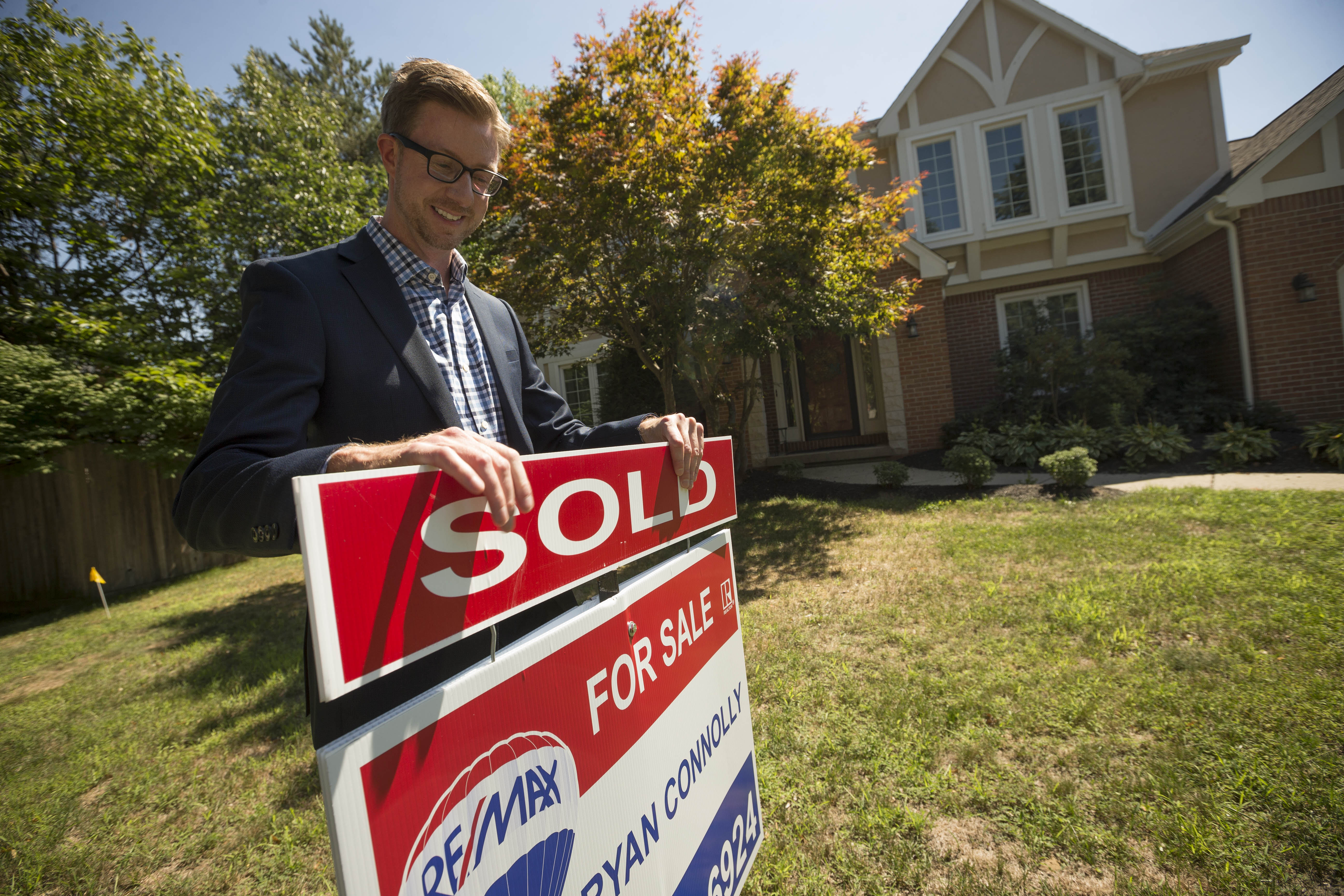 Ryan Connolly, associate real estate broker with Re/Max, outside a home he sold in Getzville.  (Derek Gee/Buffalo News)