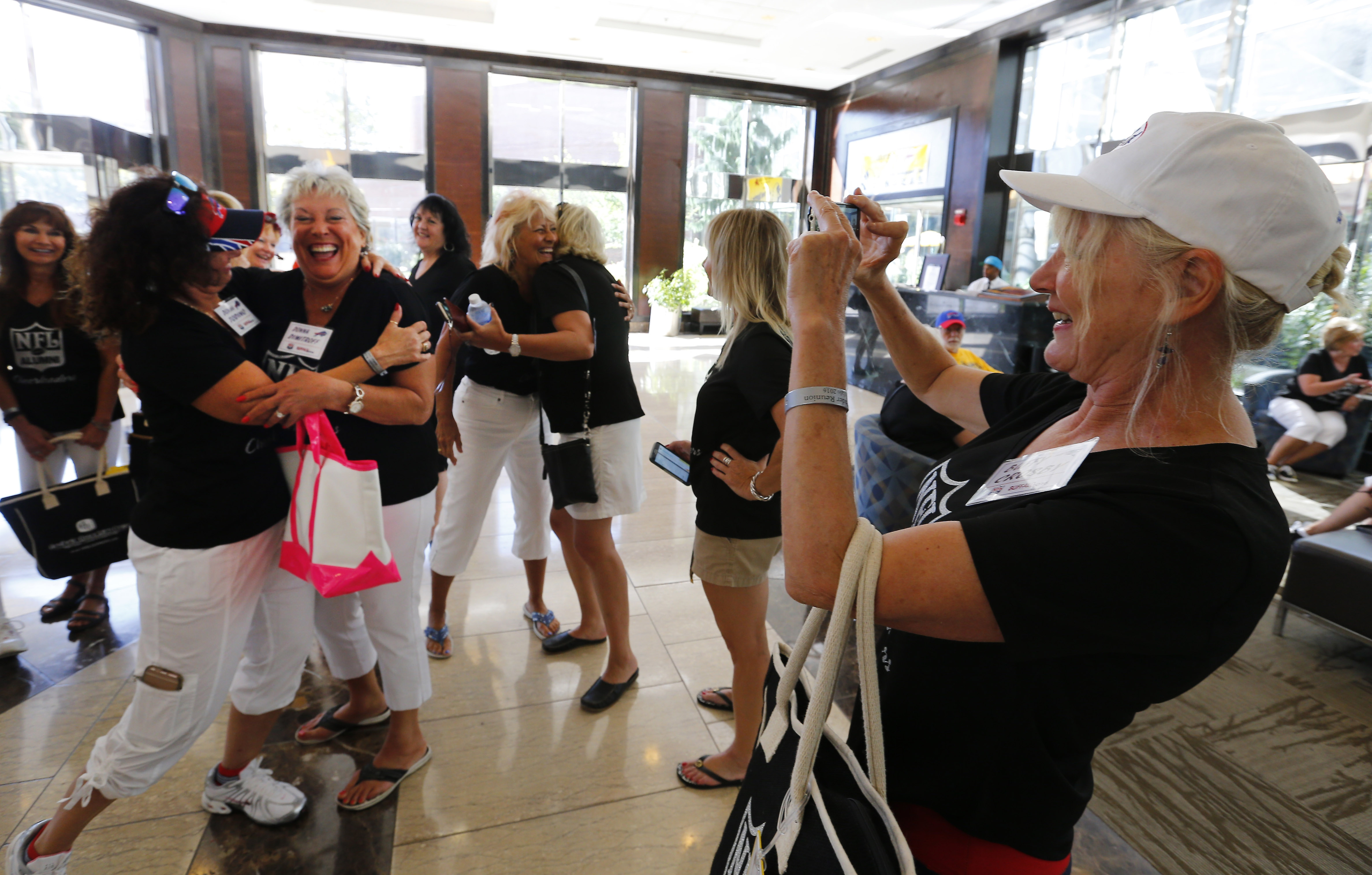 Former New England Patriots cheerleader Buffy Crosby, right, snaps a photo of former Jills cheerleaders Donna Todino, left, and Donna Dimitroff, second left, before a trip to Niagara Falls.
