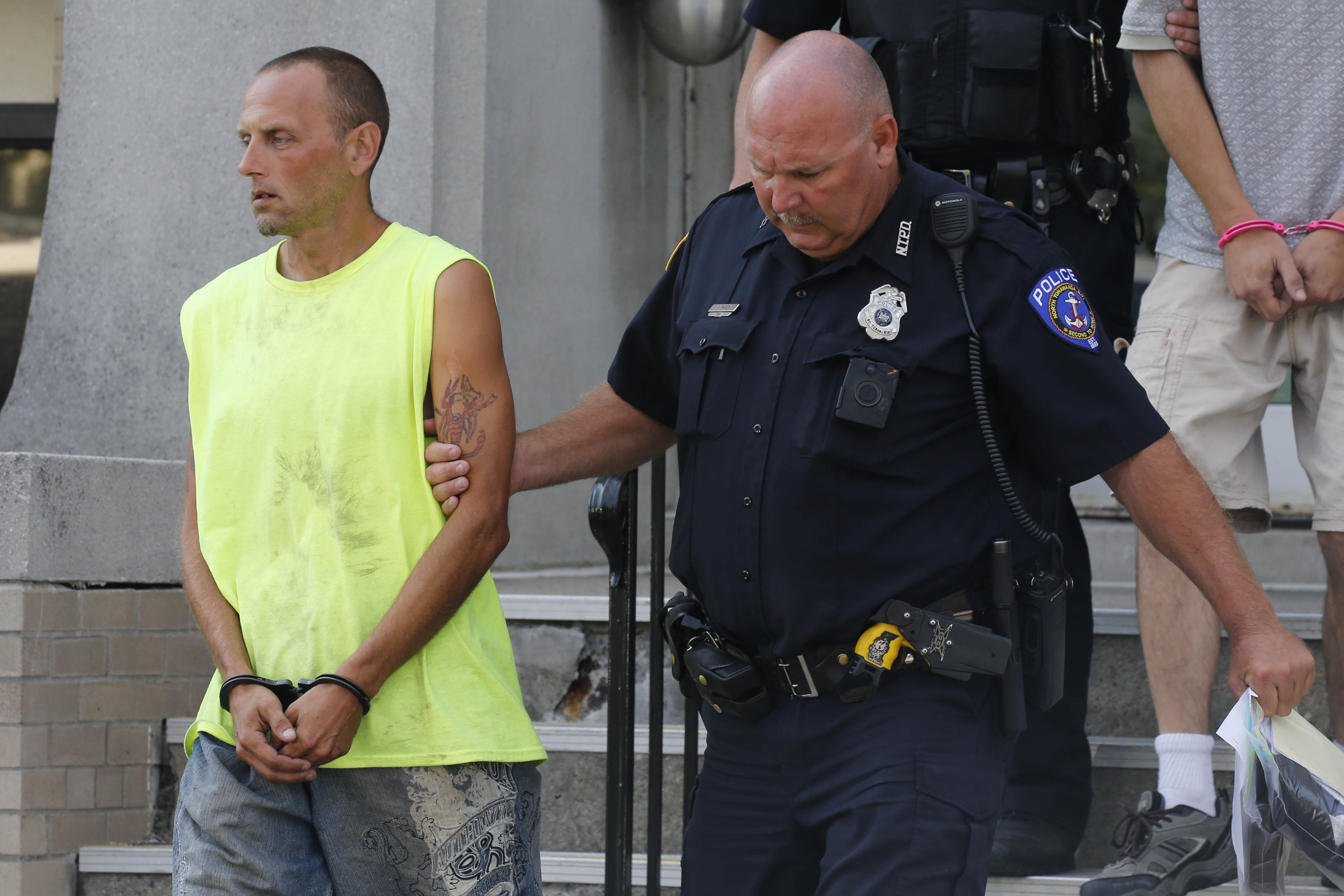 Matthew Jurado, 39, is led out of the North Tonawanda Police Station by an officer on Friday, Aug. 5, 2016 after being arraigned for intentionally starting a fire in the home of his neighbor, a black firefighter who had just received racist threats. (Photo by Derek Gee)