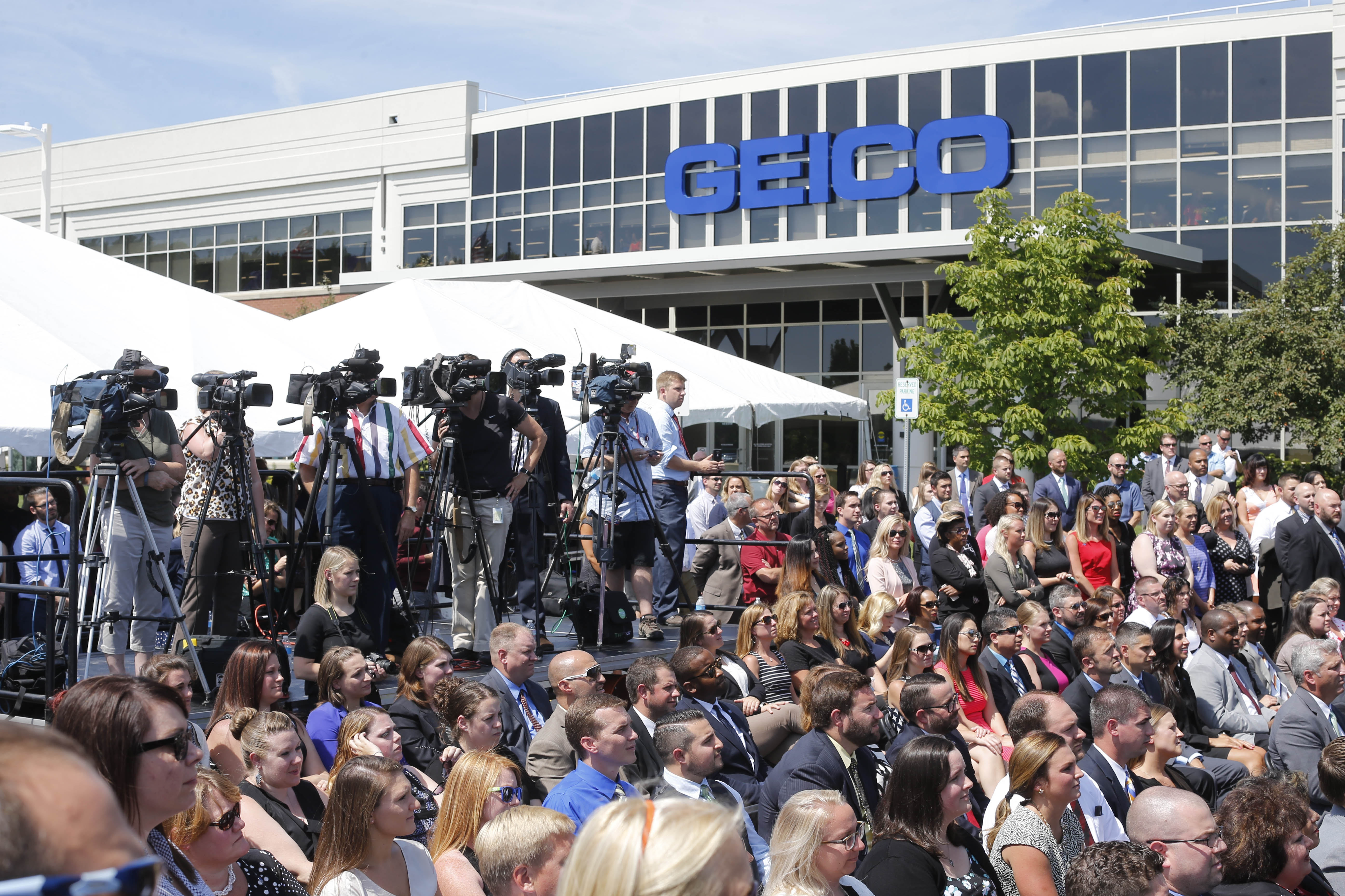 News media and others gather outside the GEICO office in Amherst Tuesday for the announcement that the insurer will add 600 new jobs, bringing its total to about 3,400.