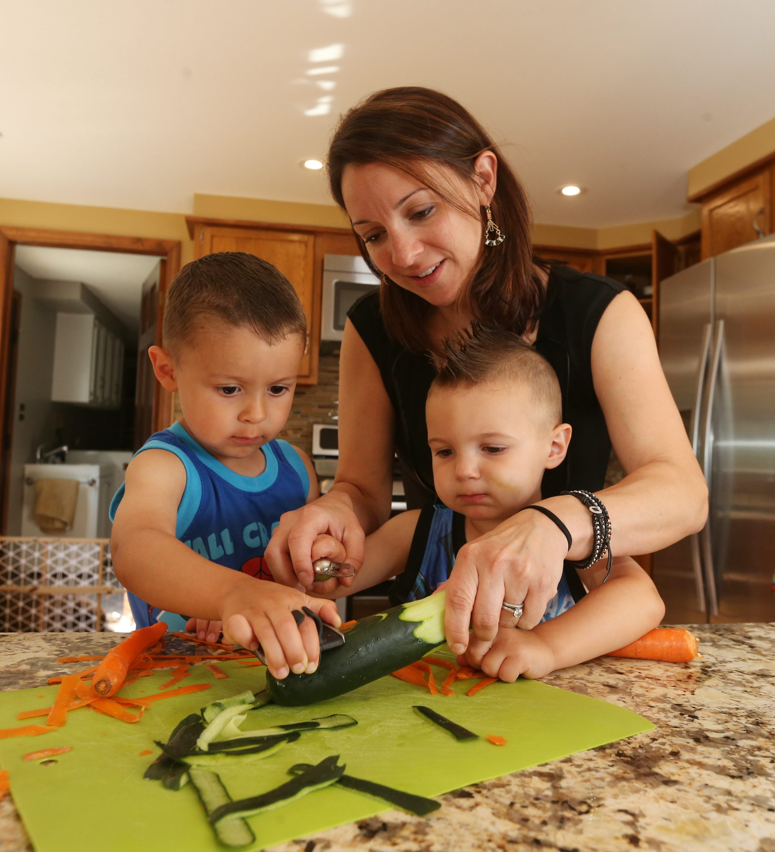Josette Hickey, of Williamsville, involves her children in food preparation which helps to make them more enthusiastic about what they are eating. Corey, 4, left, and Garett, 2, help to peel carrots and a cucumber. They have their own stools for helping at the kitchen counter.
