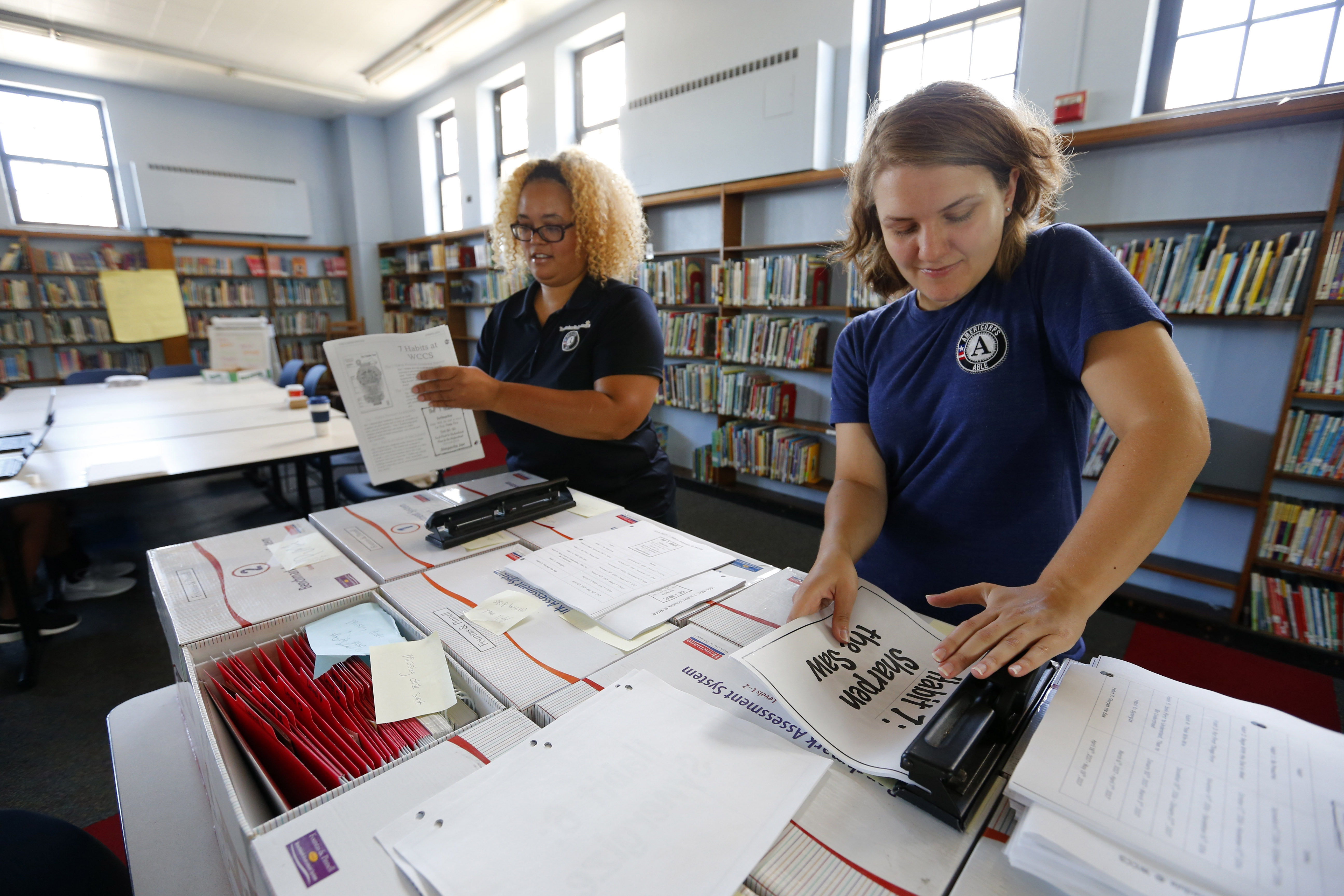 AmeriCorps members Jemaris Ellis, left, and Alyssa Kocher, right, punch holes into papers for binders for the upcoming school year at Westminster Charter School in Buffalo on Friday, August 19, 2016. (Mark Mulville/Buffalo News)