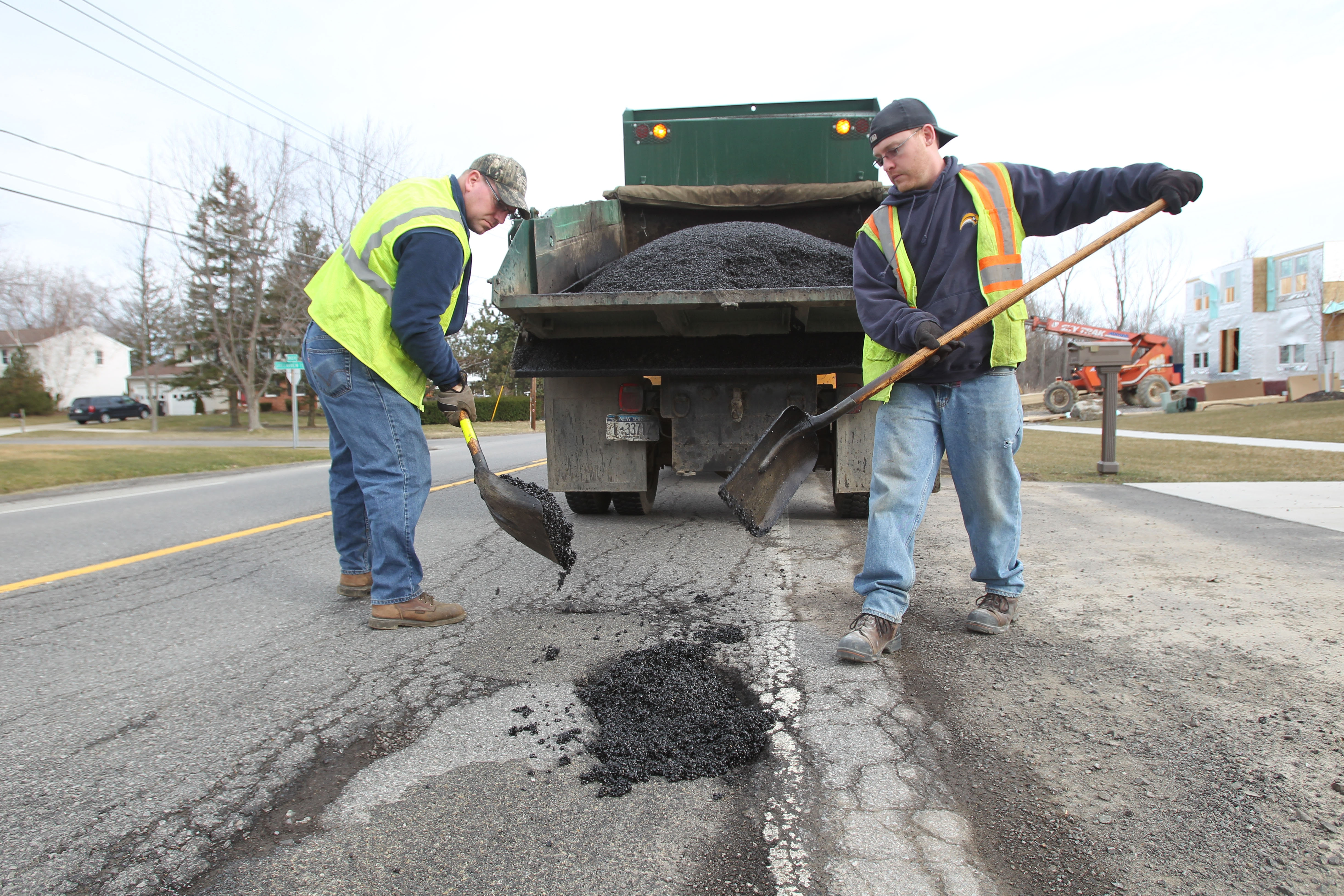Erie County Highway workers Bryan Webber, left and Jeff Mooney work on Rogers Road in Hamburg in 2012. (Sharon Cantillon/Buffalo News)