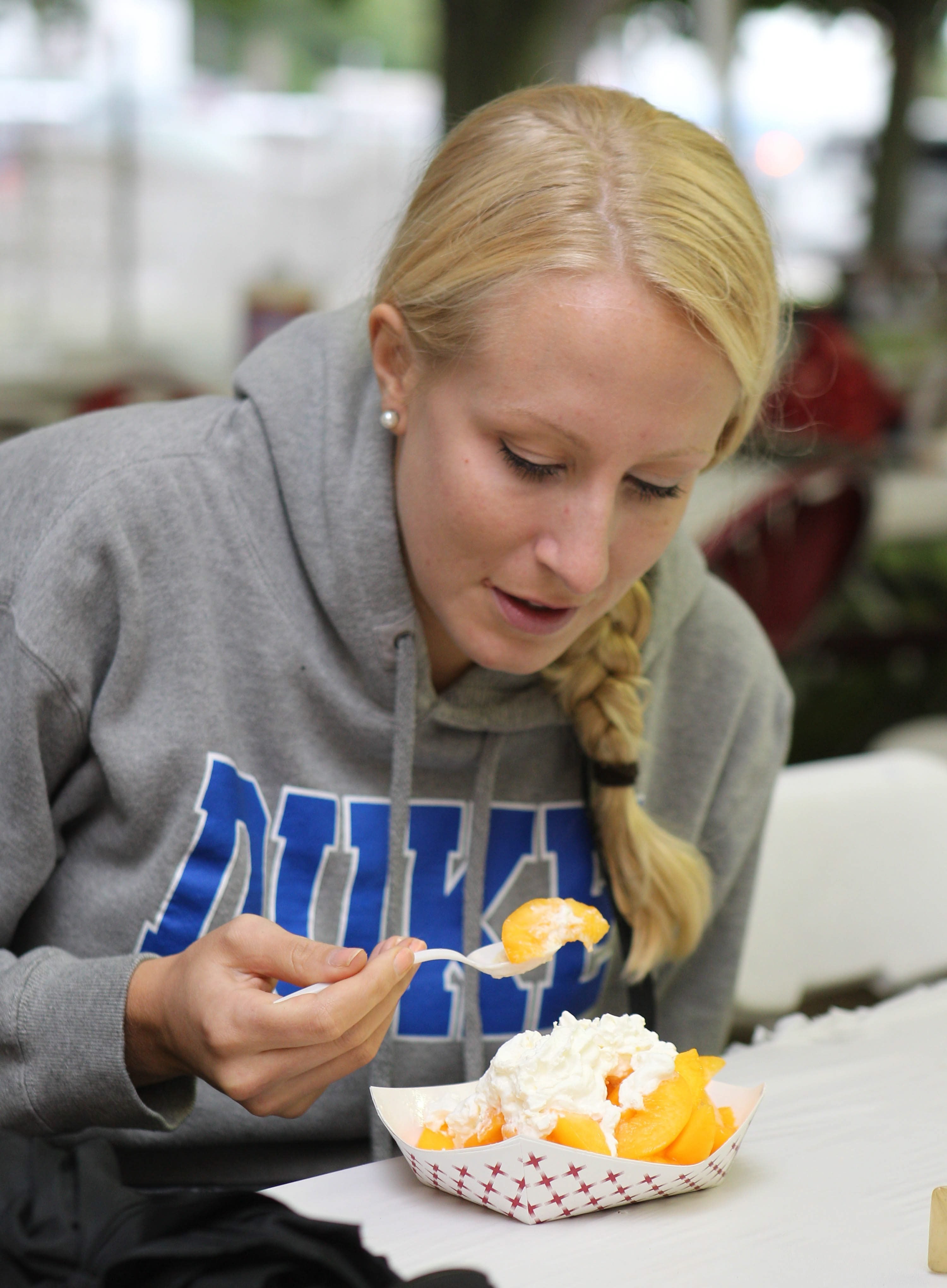 Haley Gow of Kenmore enjoys a peach cobbler sold by the Lewiston Kiwanis Club at the Niagara County Peach Festival in this file photo from Sept. 7, 2013. (Sharon Cantillon/Buffalo News)