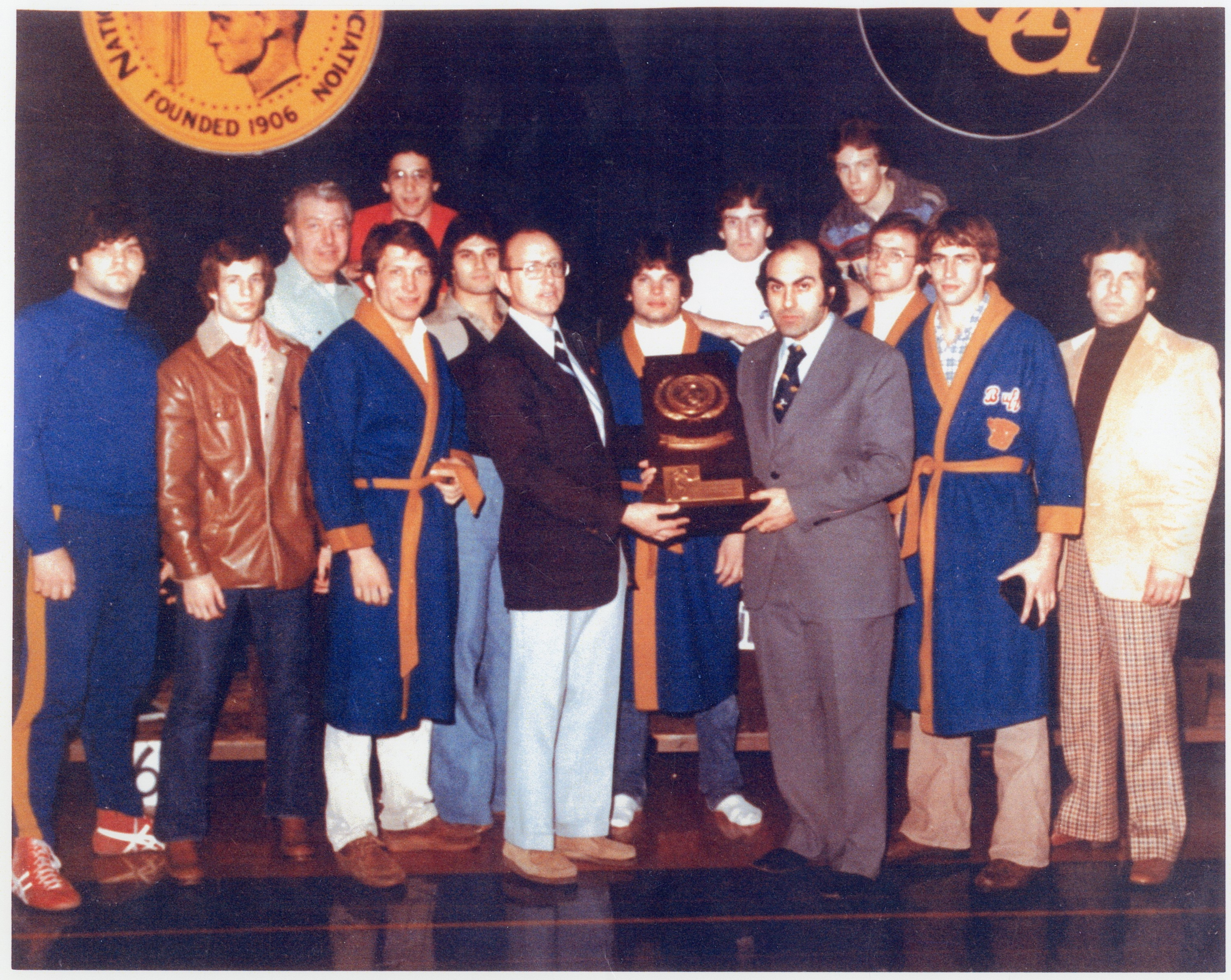 Ed Michael, in gray suit, and his UB wrestling team are presented the 1977-78 NCAA Division III Wrestling championship plaque.