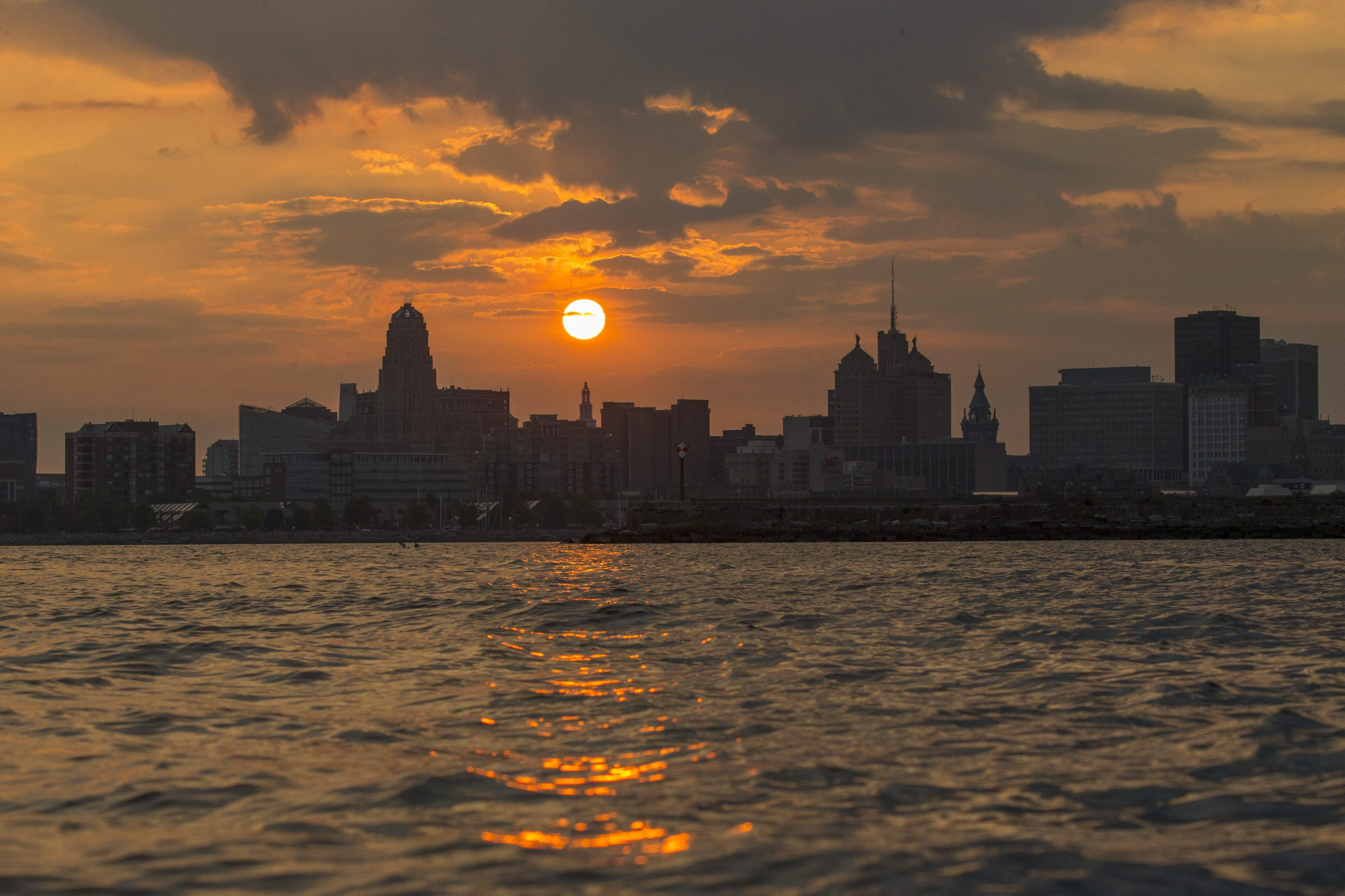 The sun rises behind the city skyline earlier this summer.  (Photo by Derek Gee)