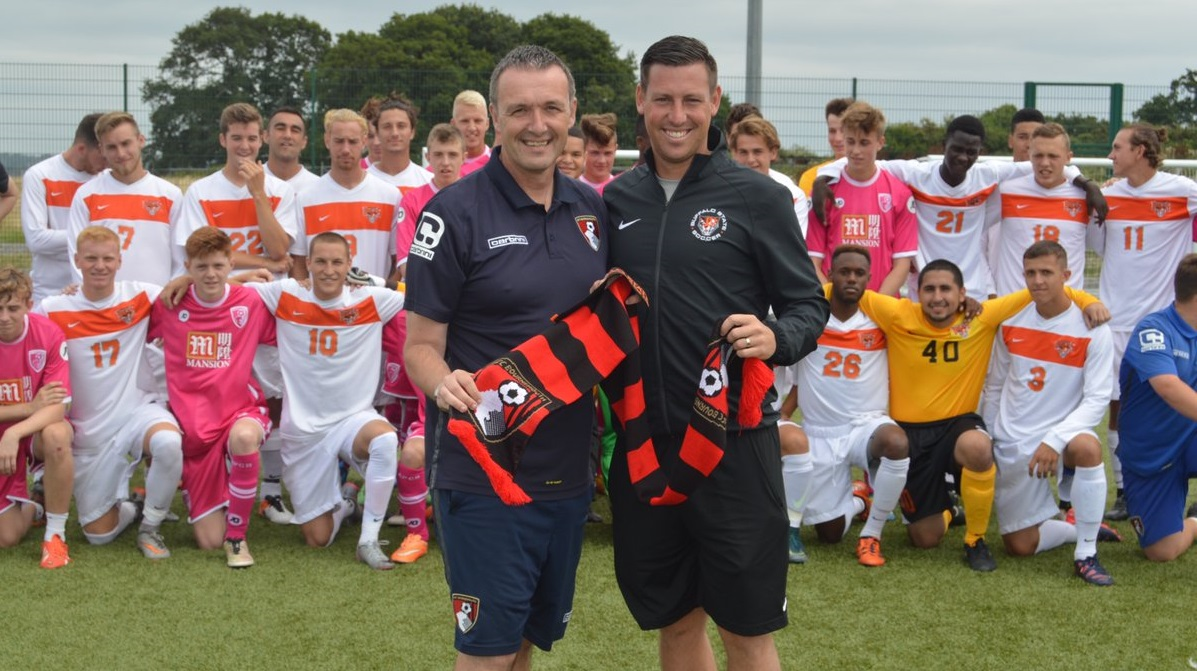 Buffalo State men's soccer head coach Mark Howlett, right, poses with both Bournemouth U18s and his Buffalo State Bengals. (via AFC Bournemouth)