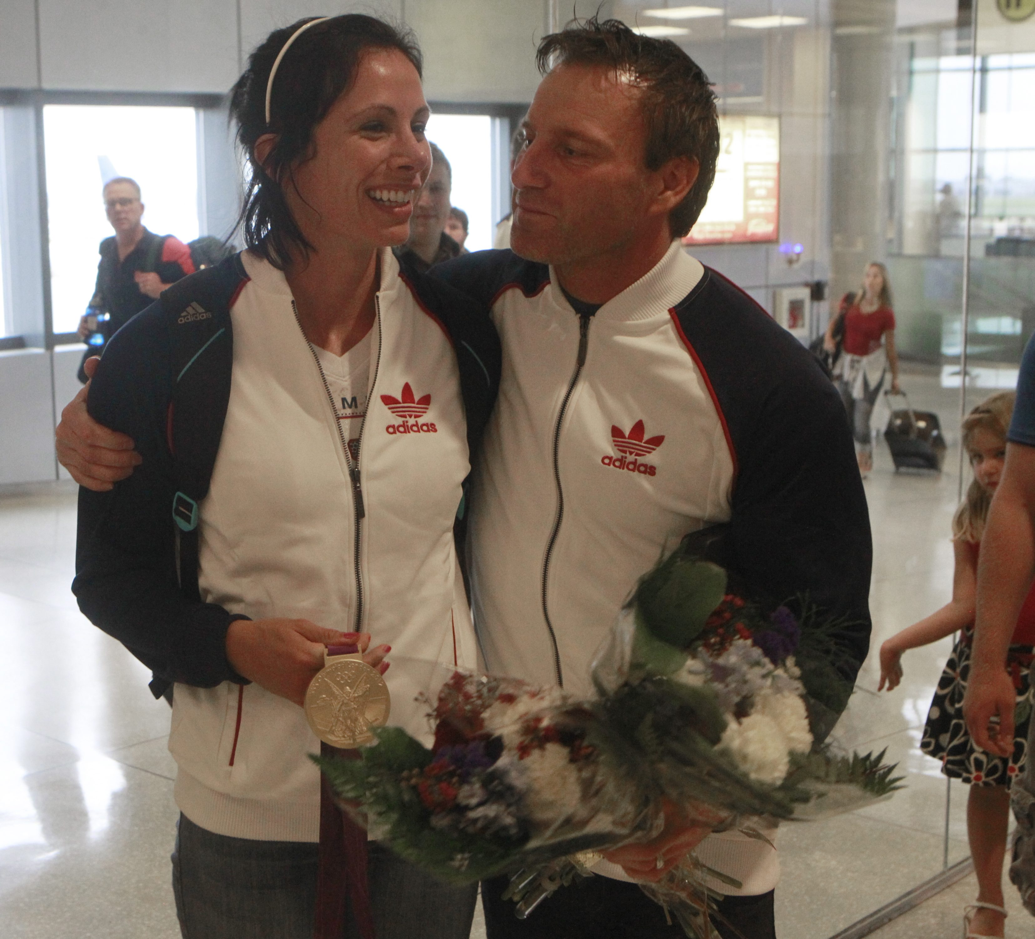 Pole vaulter Jenn Suhr and her husband and coach Rick arrive at the Buffalo Niagara airport following Jenn winning gold in London. (John Hickey / Buffalo News)