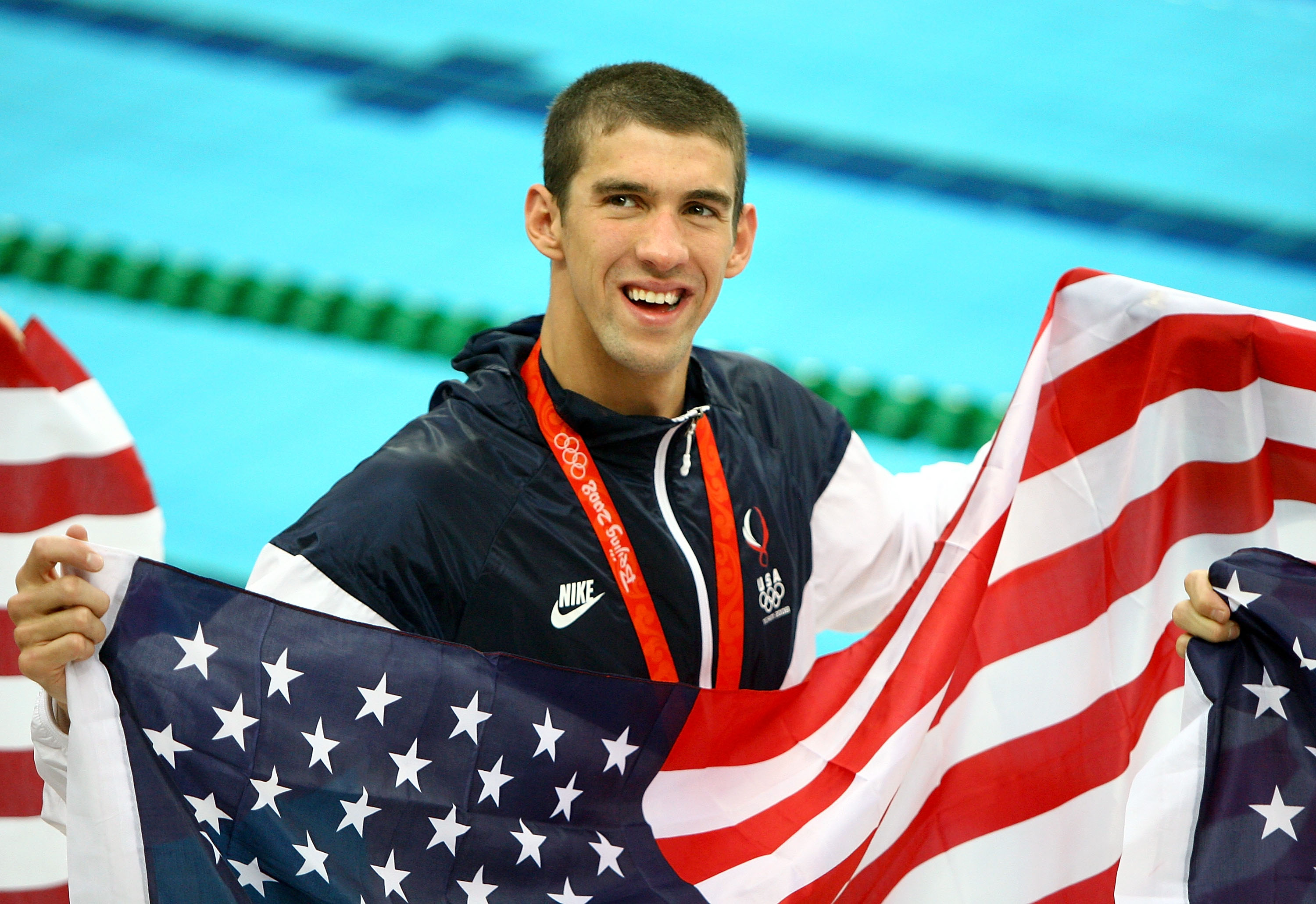 BEIJING - AUGUST 17: Michael Phelps of the United States smiles with the American flag as he wears his eighth gold medal after the Men's 4x100 Medley Relay at the National Aquatics Centre during Day 9 of the Beijing 2008 Olympic Games on August 17, 2008 in Beijing, China. (Photo by Adam Pretty/Getty Images)