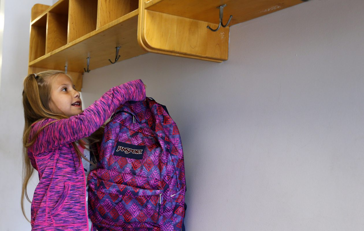 Jessica Cwierley hangs her backpack at the Amherst Youth and Recreation Center. (Mark Mulville/ News file photo)