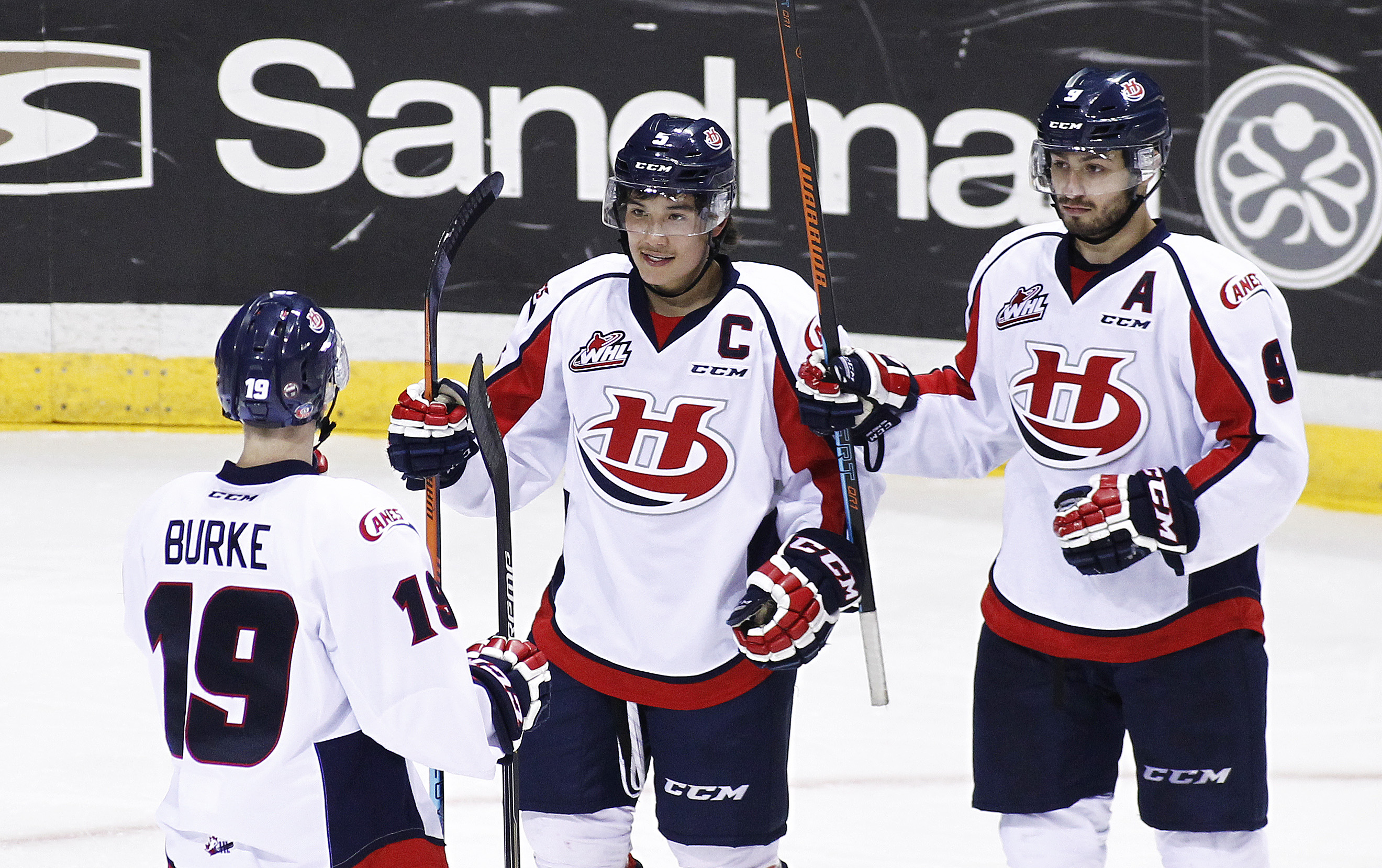 VANCOUVER, BC - OCTOBER 28: Tyler Wong #5 of the Lethbridge Hurricanes celebrates his goal against the Vancouver Giants with teammates Giorgio Estephan #9 and Brayden Burke #19 during the first period of their WHL game at the Pacific Coliseum on October 28, 2015 in Vancouver, British Columbia, Canada. (Photo by Ben Nelms/Getty Images)