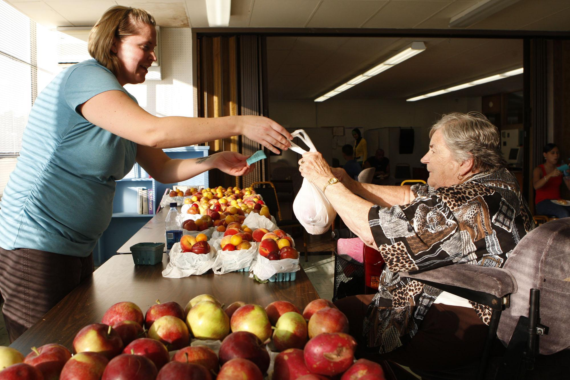 Barbara Marranca receives fresh produce from Christel VanAllen provided by Dan Tower Farm in Youngstown at the Good for the Neighborhood health initiative created by the Independent Health Foundation. Four similar programs are planned for this month. (Buffalo News file photo)