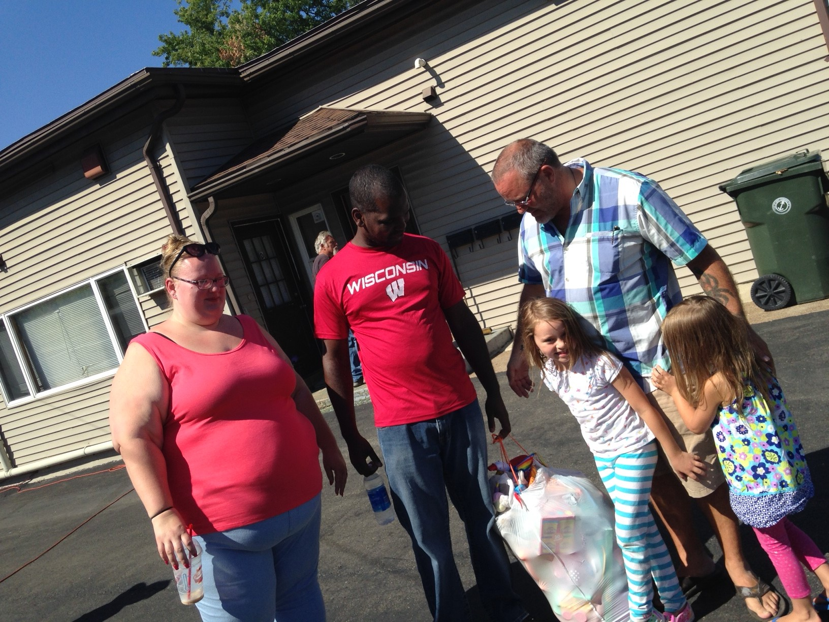 Amanda and Kenneth Walker, left, accept a bag full of toys for their daughters from John Karcz and his daughters, Anastasia and Isabella, right. The Walkers lost most of their possessions in a fire at their apartment Wednesday, two days after Kenneth Walker received a threatening, racist letter demanding he resign from Gratwick Hose Volunteer Fire Company. (Lou Michel/Buffalo News)