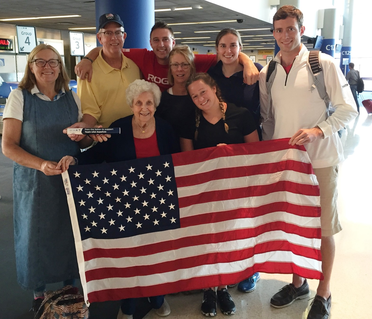 The Regan family poses with an American flag before boarding their flight to Rio.