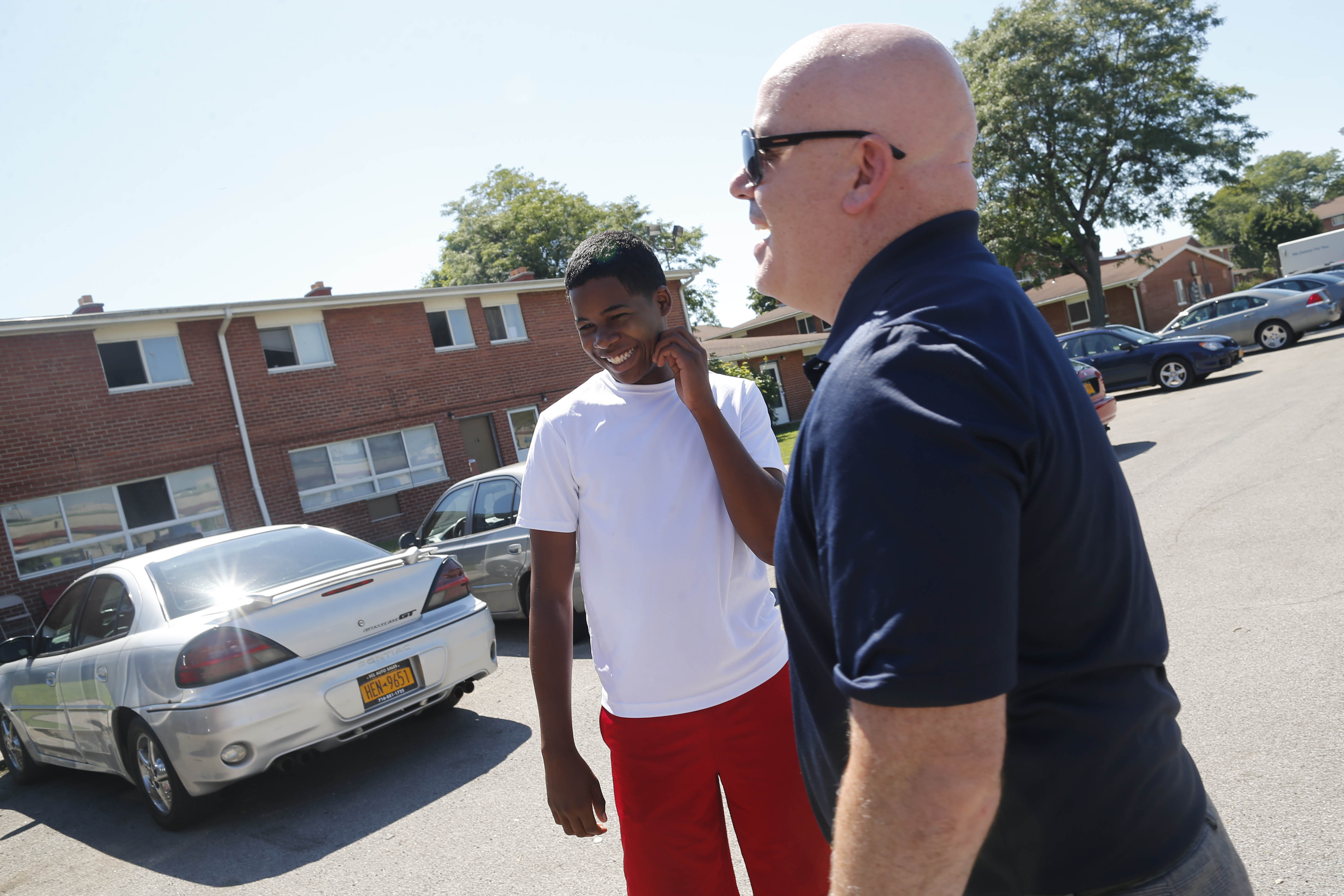 John Starkey, the new principal of Lafayette High School, chats with incoming freshman Jabneel Calderon Cruz outside his apartment at Towne Apartments before the start of the school semester. (Derek Gee/Buffalo News)