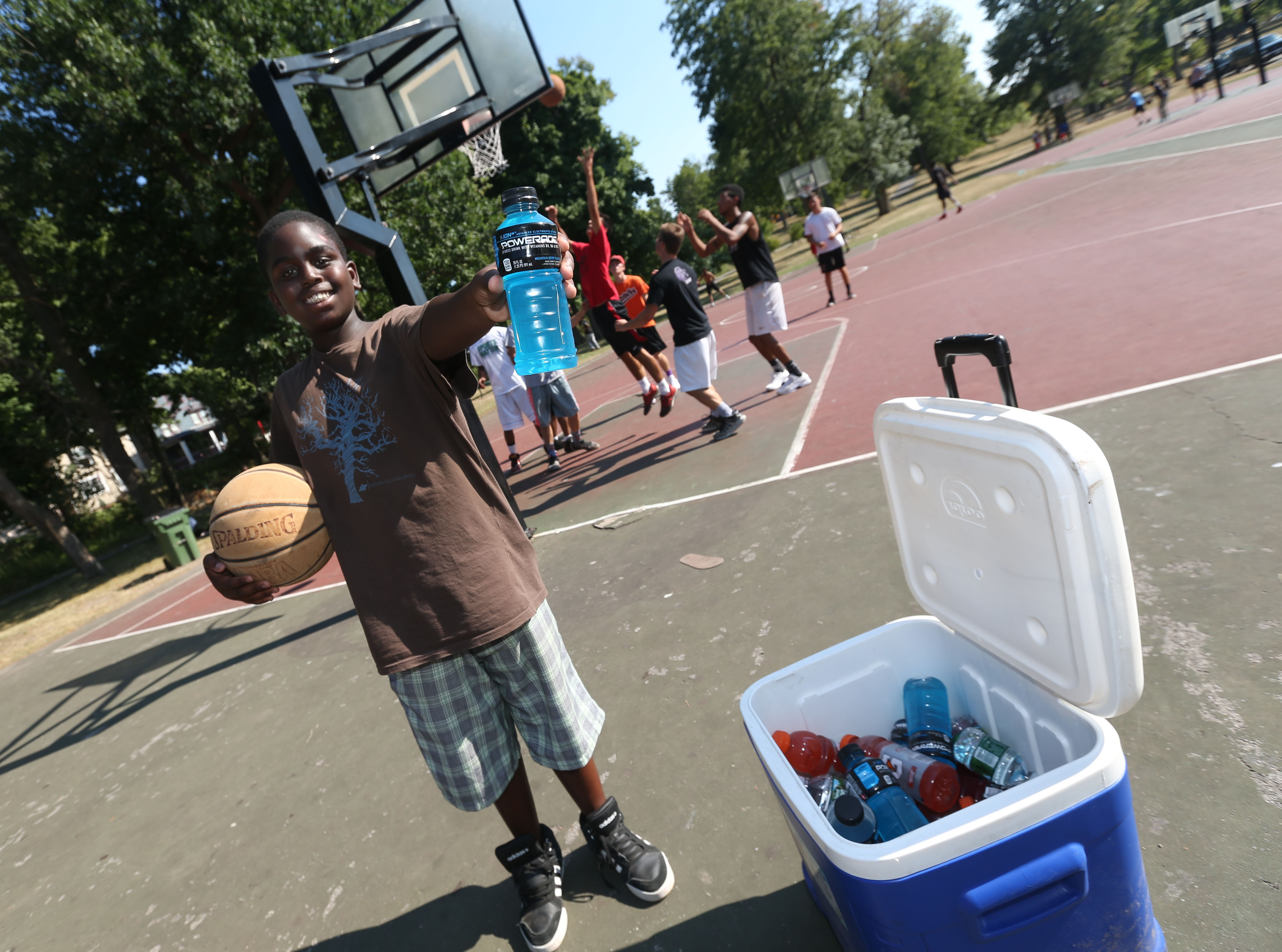 Marcelino Long, 10, of Buffalo sells energy drinks and water to the basketball players all summer long. He's saving up to buy a hover board. (Sharon Cantillon/Buffalo News)