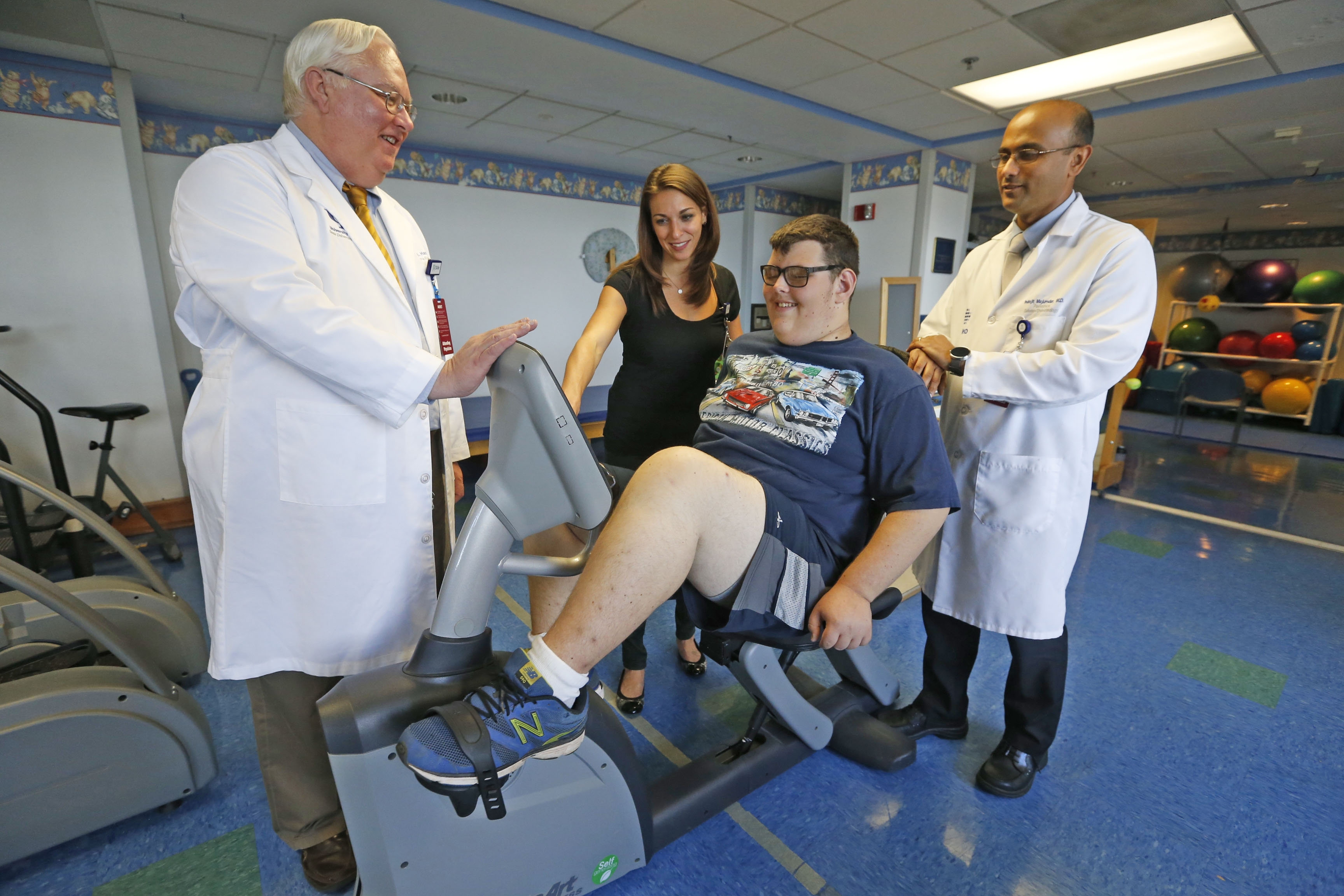 """From left, Dr. Carroll """"Mac"""" Harmon, chief of surgery, Lauren Dunaway, physical therapist, and Dr. Indrajit Majumdar, an endocrinologist, monitor Ethan Milich, 18, of Amherst, as he exercises on a recumbent bike in the physical therapy department at Women & Children's Hospital. (Robert Kirkham/Buffalo News)"""