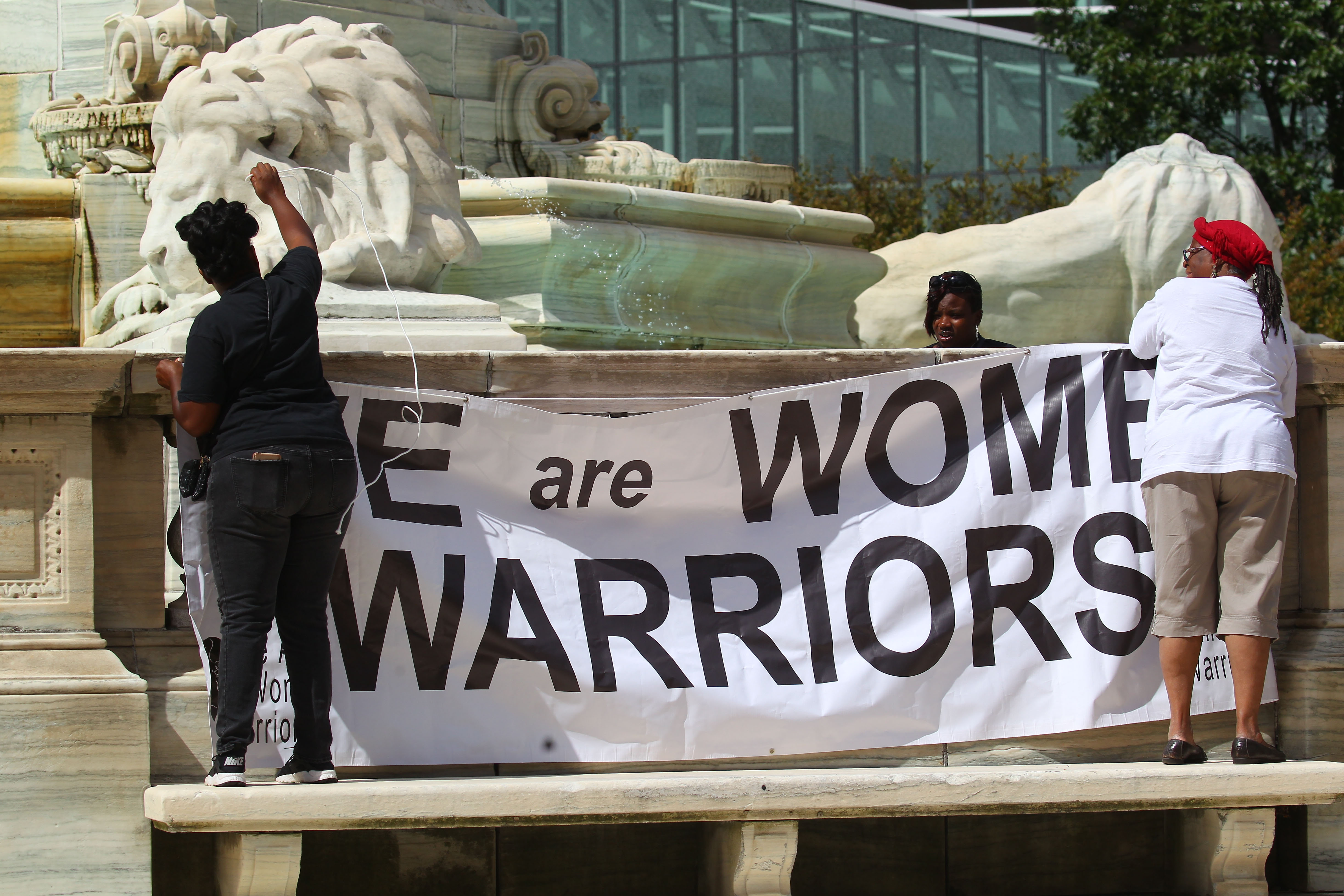 Mark Mulville/Buffalo News  From left, Tamell Walker, Rebecca Brooks and Charlene Miller put up a banner before a rally Friday against violence in Niagara Square.