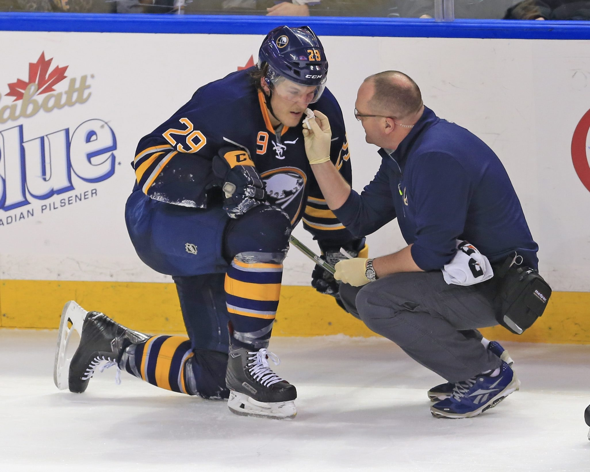 Jake McCabe recieves medical attention from trainer Tim Macre. (Harry Scull Jr./Buffalo News)