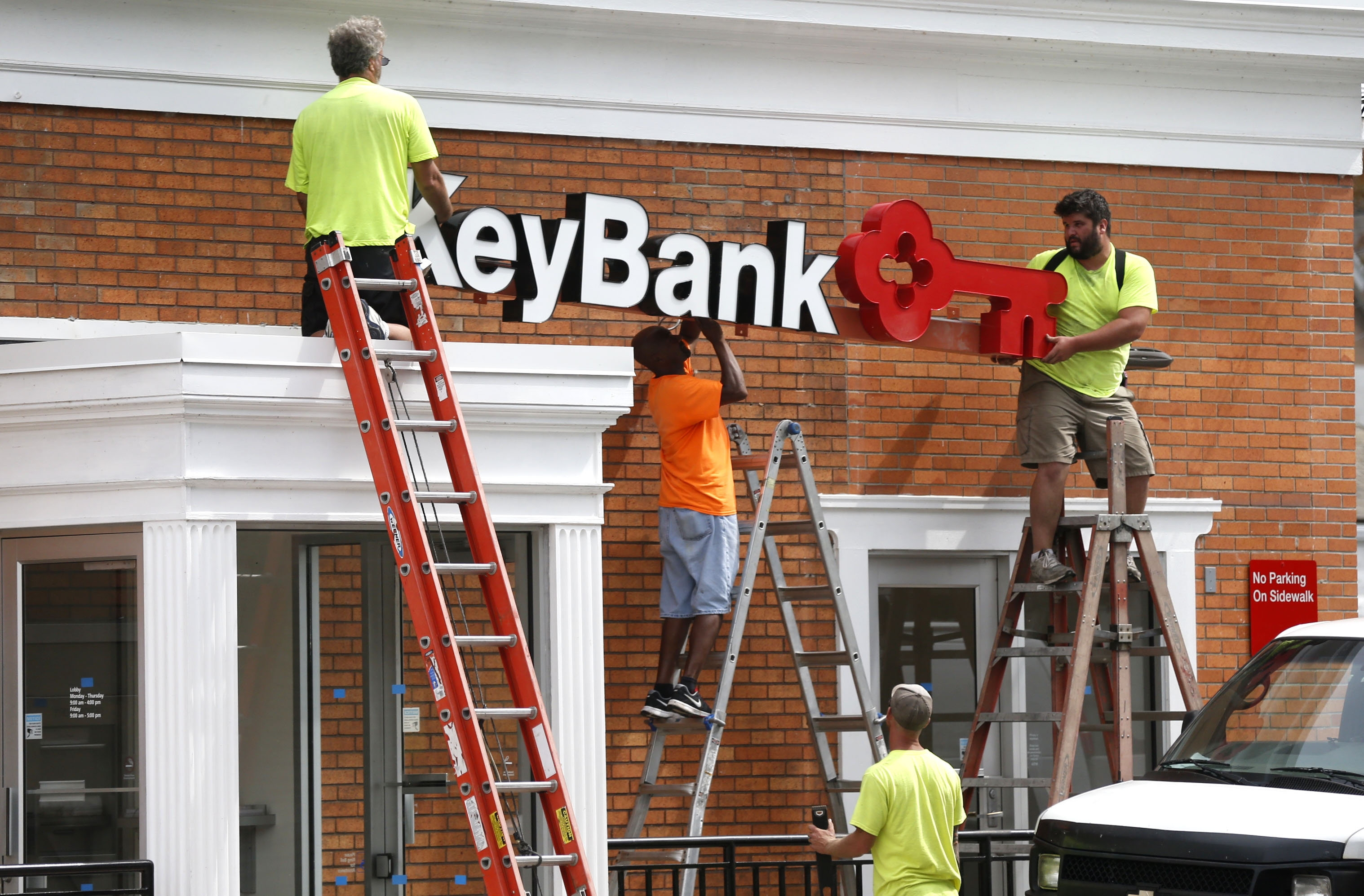 Contractors install a KeyBank sign after removing a First Niagara logo on a branch on Clinton Street.
