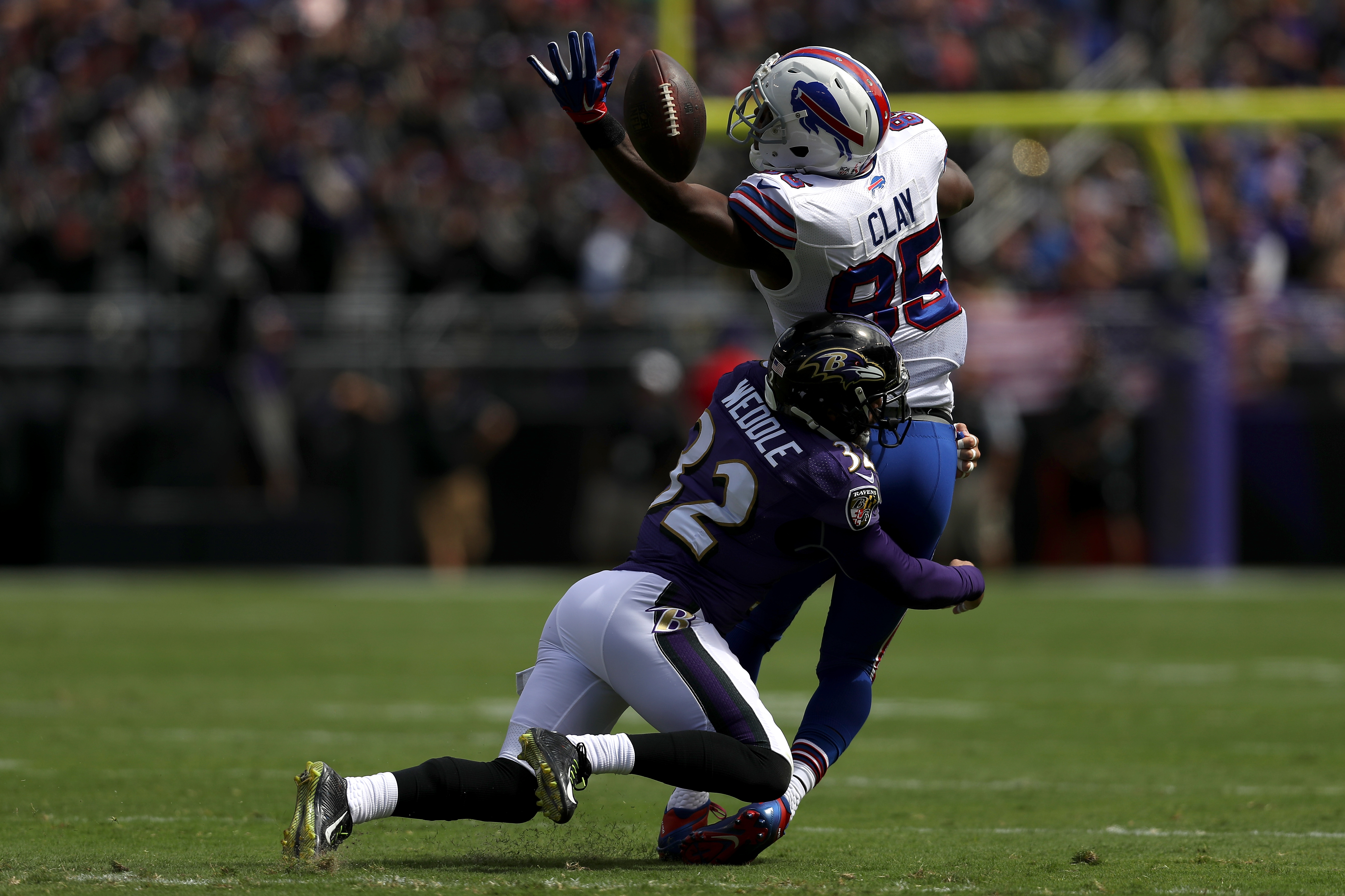 Eric Weddle of Baltimore tackles tight end Charles Clay as he attempts to catch the ball in the first half.