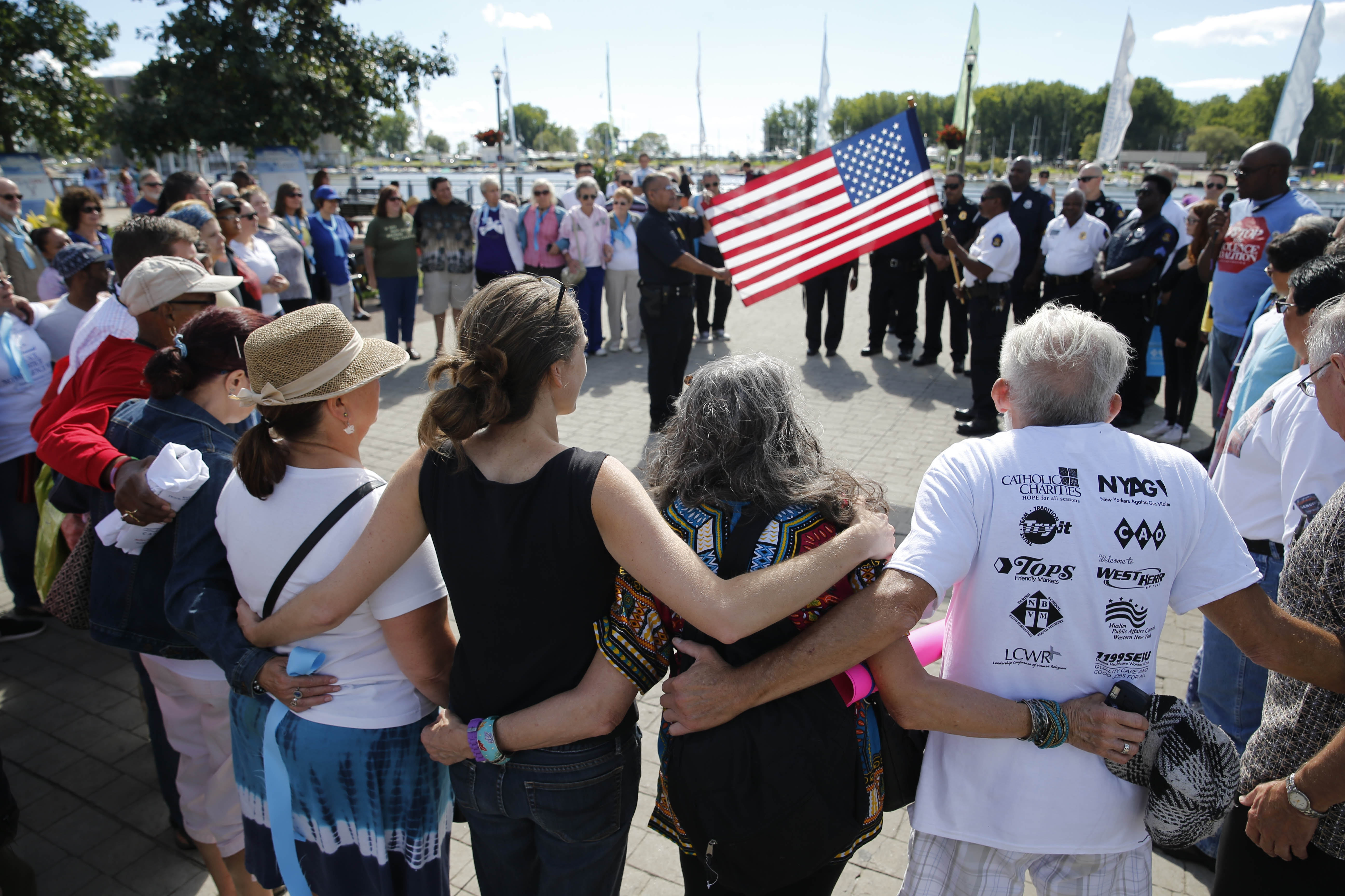 Dozens of attendees join arms for a group hug during the Peace Justice Nonviolence Festival & Walk at Canalside on Sunday.